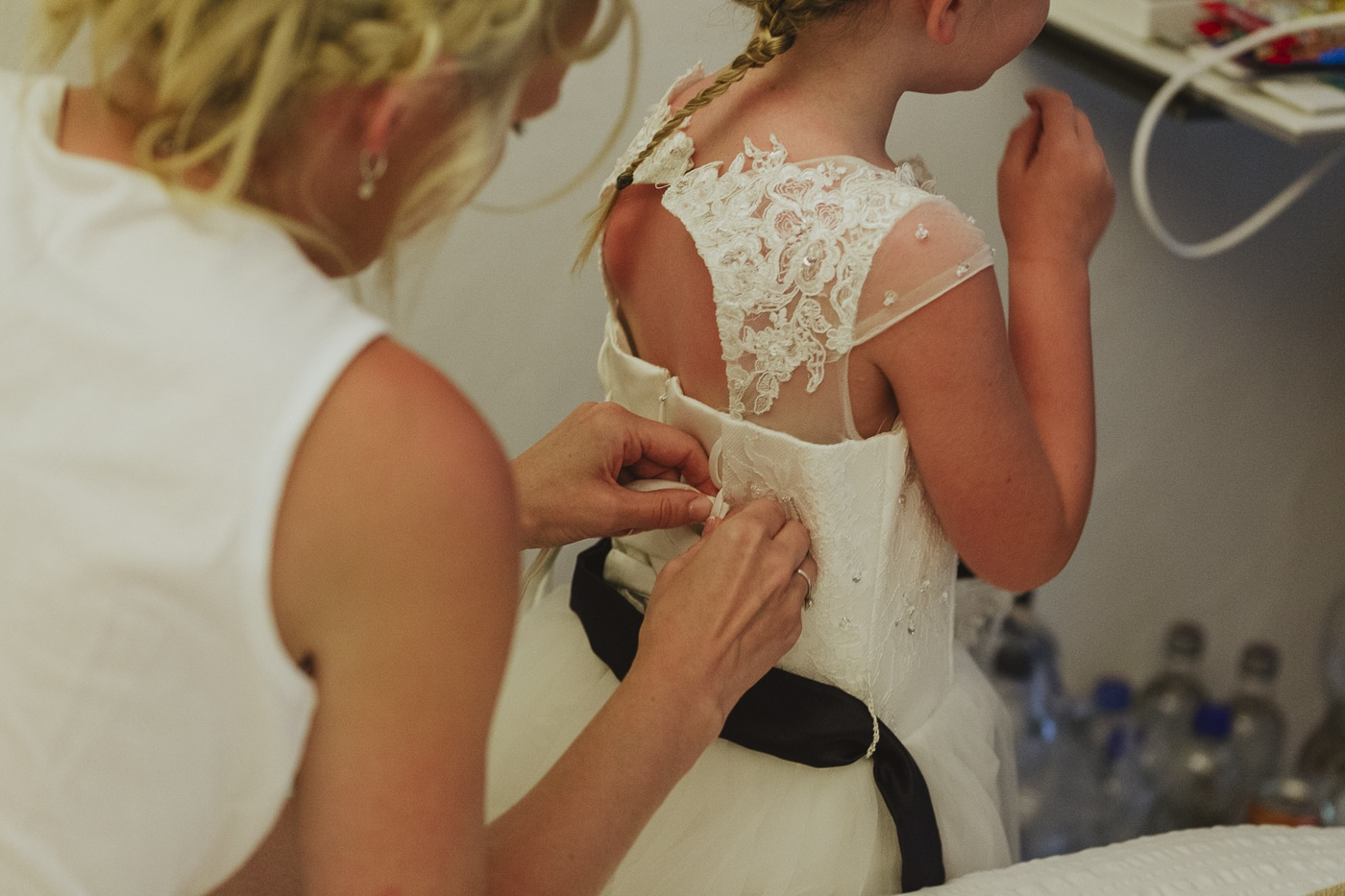 bridesmaid being tied into a white beaded and laced dress by mother