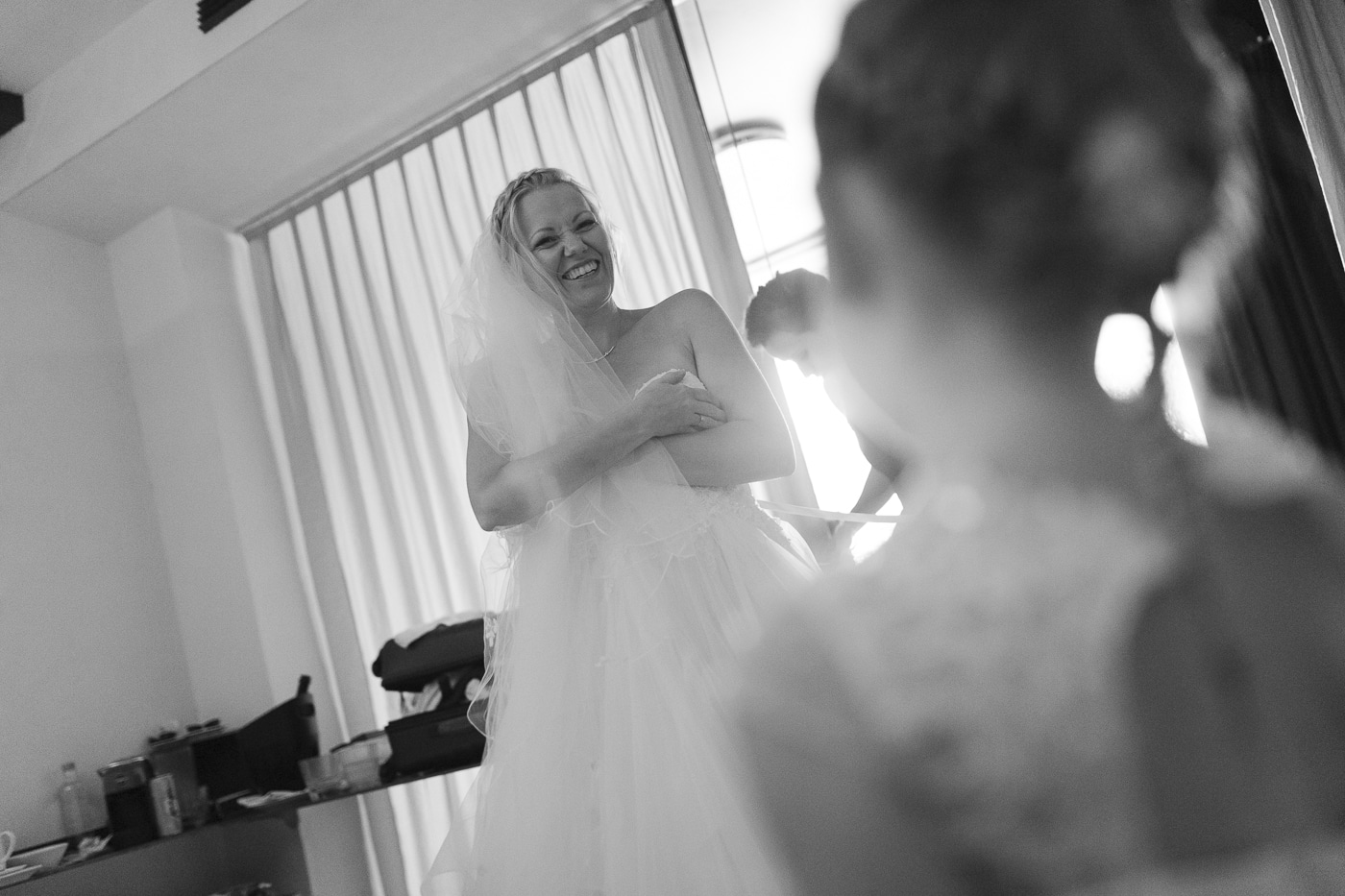 Bride in braided hair and veil holds dress up while being tied in