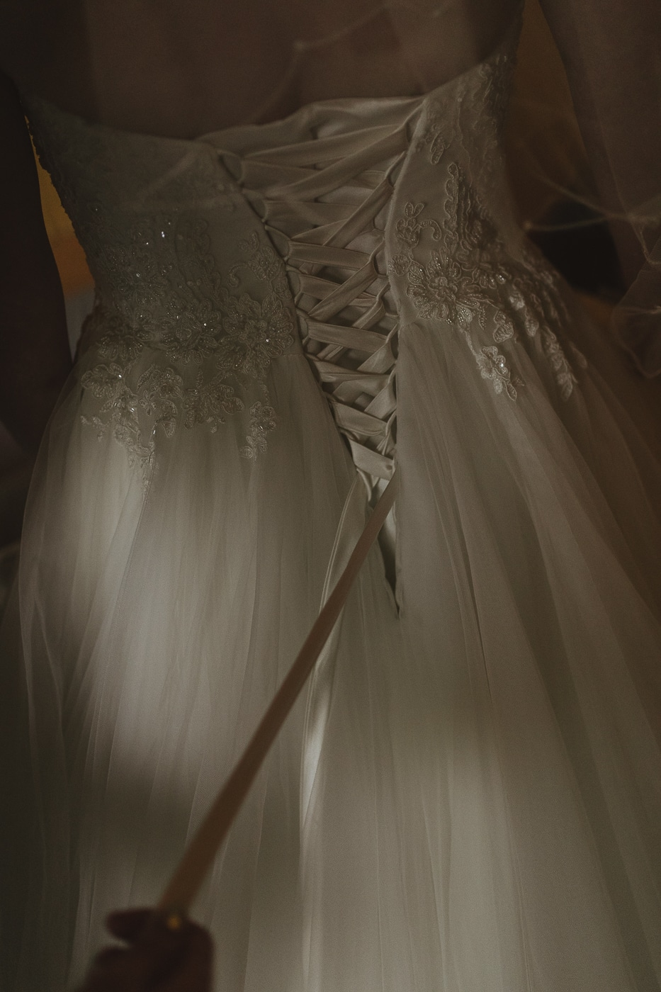Close up view of corset back dress with white ribbon and beaded detail