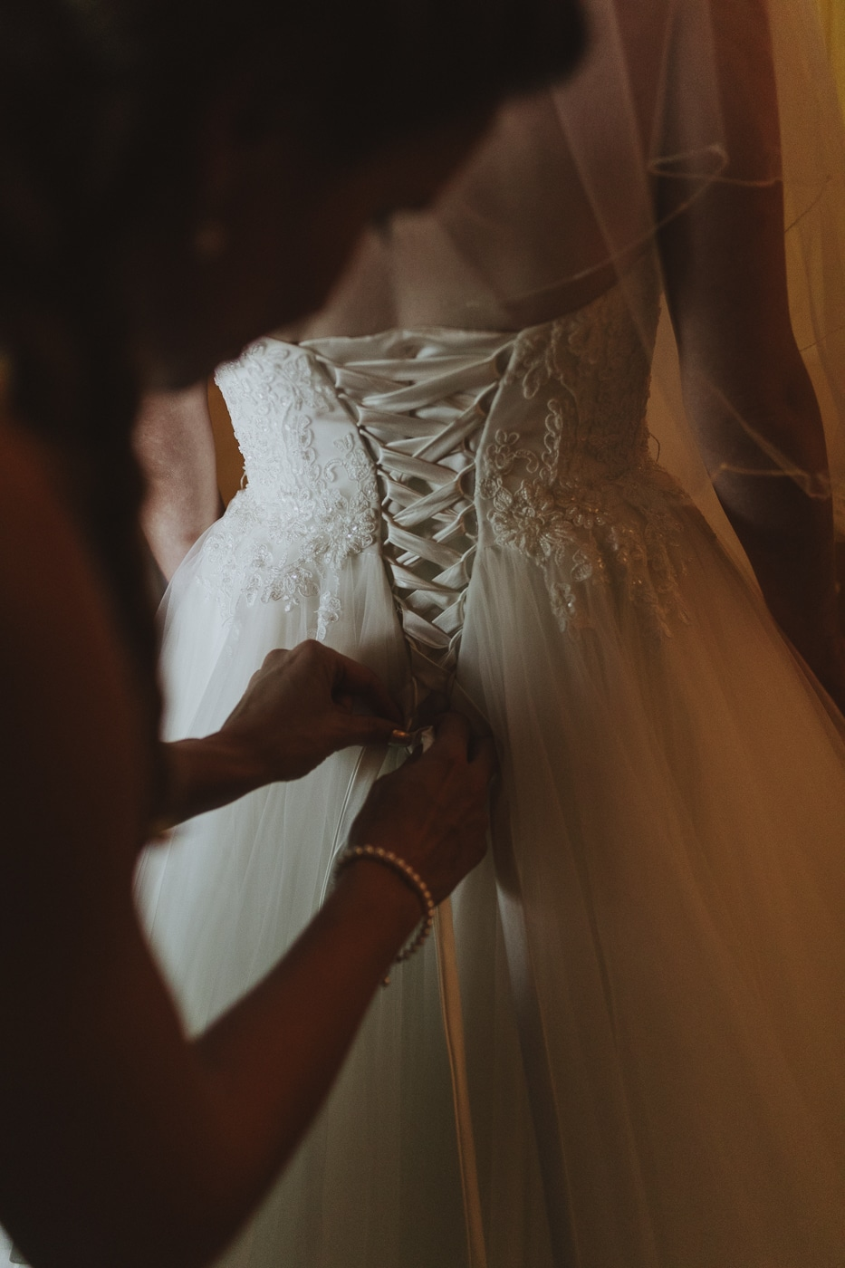 Bride with ribbon corset back dress being tied in