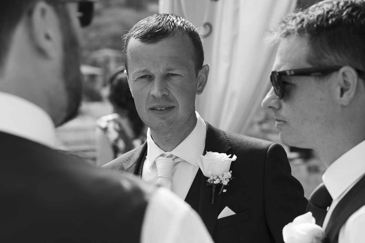 Groom with flower in his lapel talking to men with sunglasses on