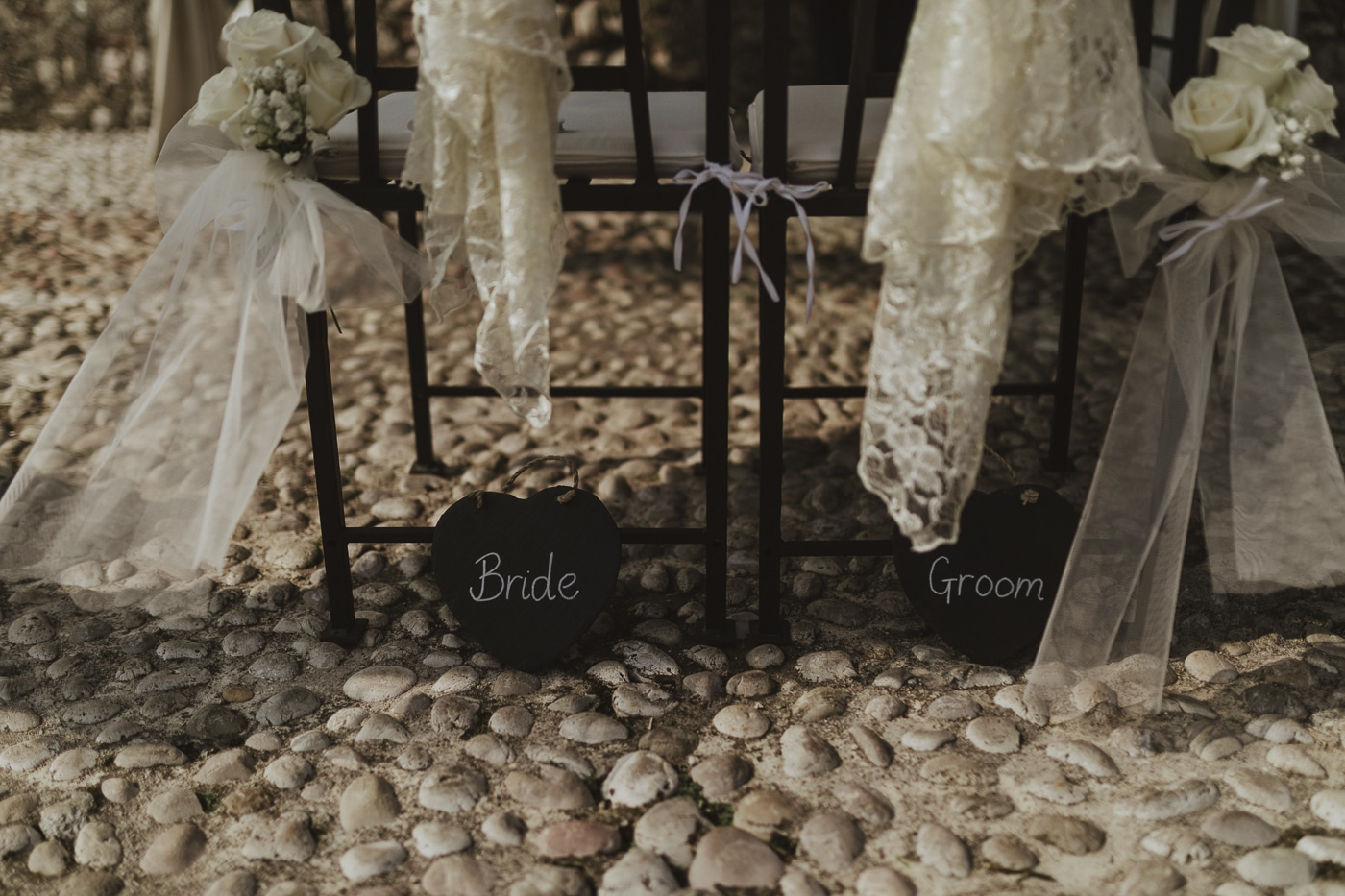 Bride and groom heart chalkboard signs at the bottom of each chair covered in lace and flowers tied to it