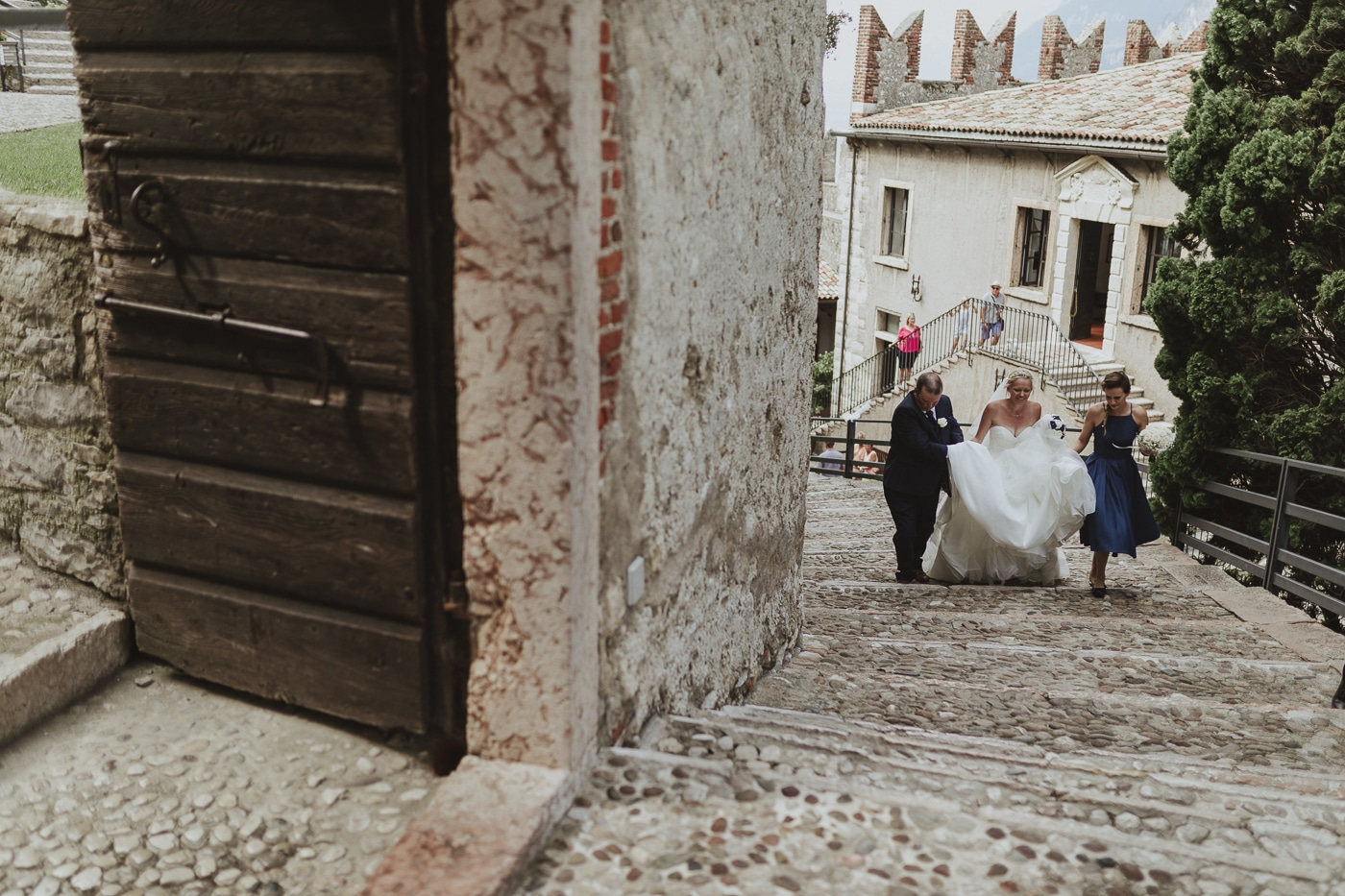 Bride and bridesmaid walk up stone steps to doorway with father holding dress