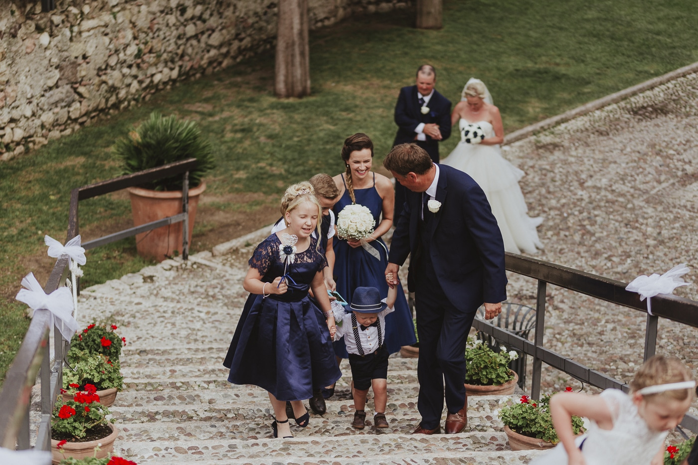 Bridesmaids and small boy in hat walk up the stone steps in front of bride and groom