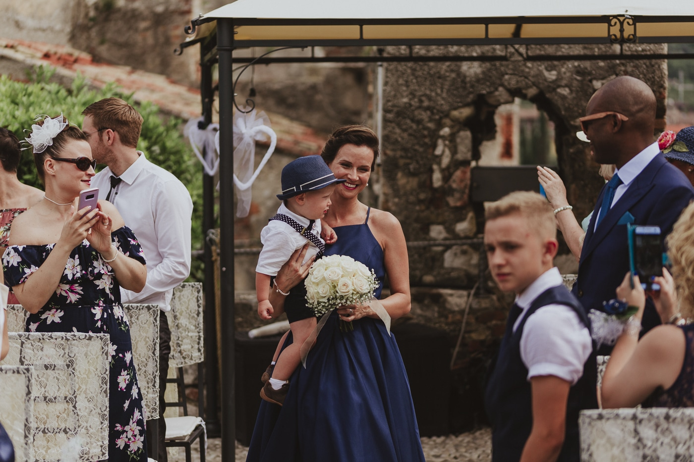 Bridesmaid and small boy in hat wait at the end of the aisle