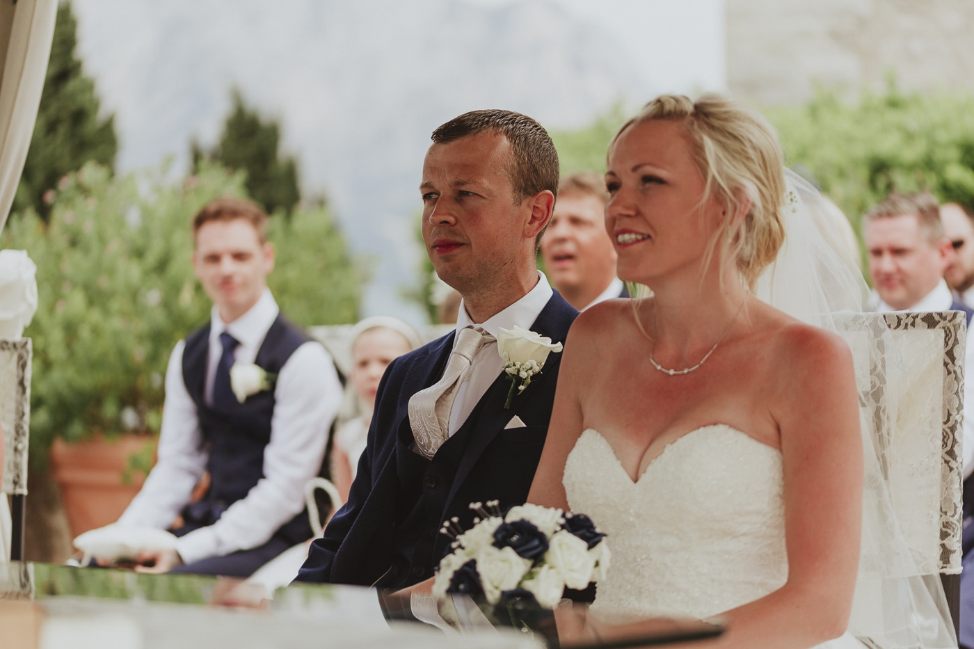 Bride and groom smiling with flowers on her lap during the wedding vows