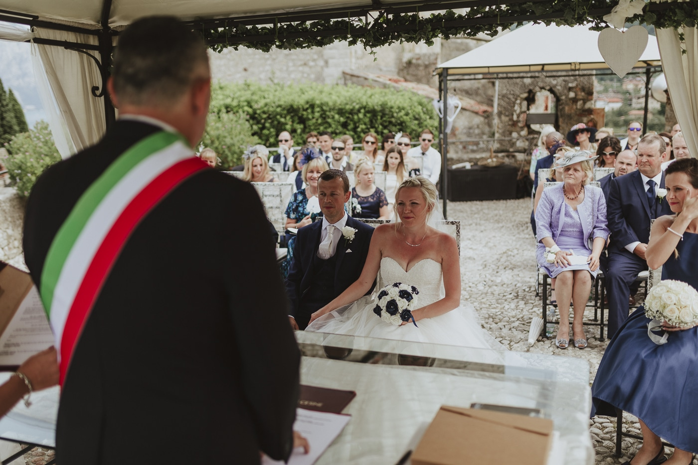Officiant holding wedding ceremony standing in front of the bride and groom with their guests in the background
