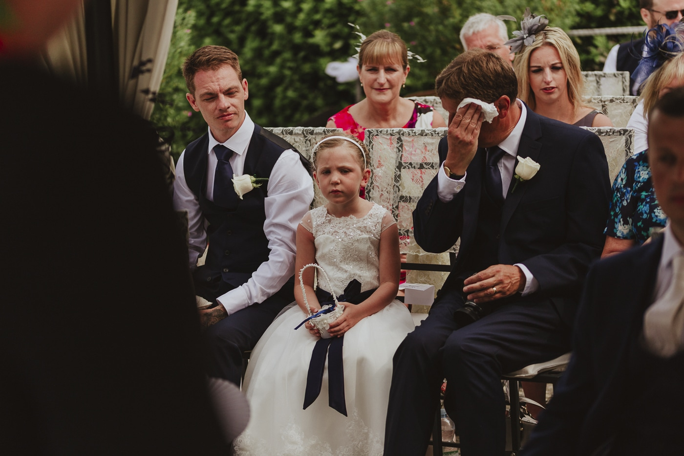 Men and small flowergirl sit patiently during wedding vows