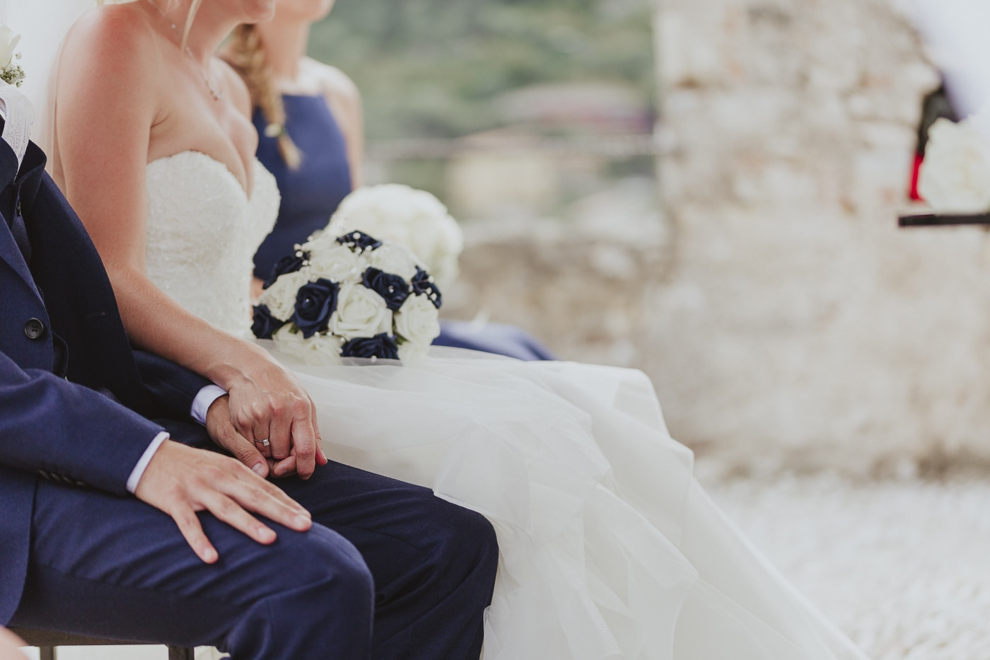 Bride with ring on her finger and flowers in her lap holds on to her grooms hand during the ceremony