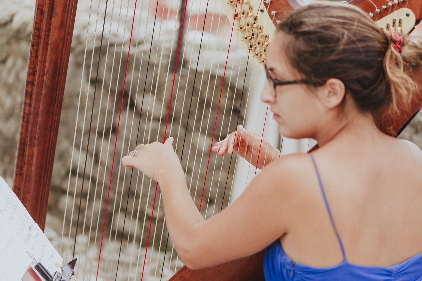 Harpest playing in blue dress and glasses with hair tied back
