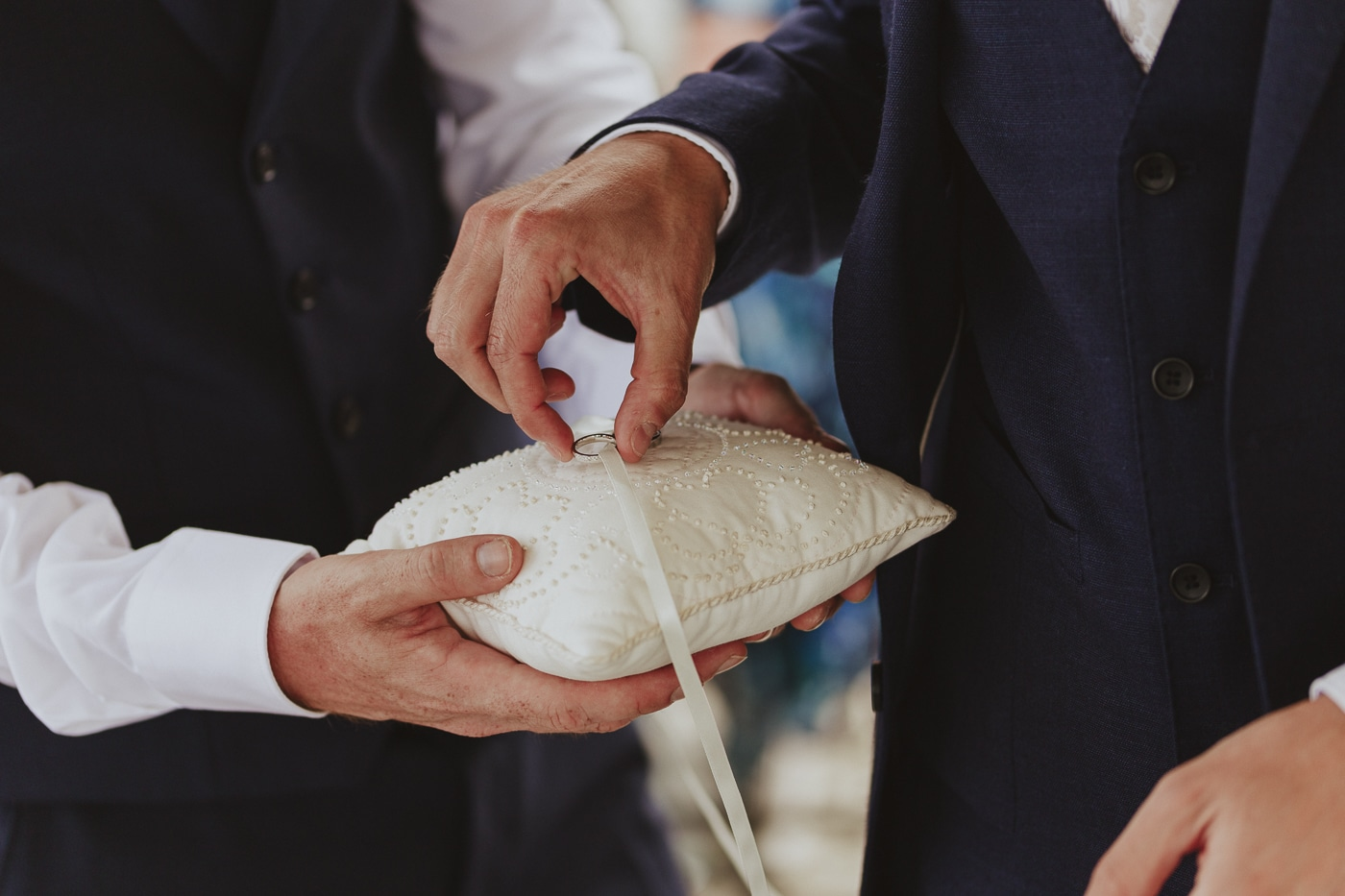 Groom taking wedding ring of white ring cushion with beading and ribbon on it