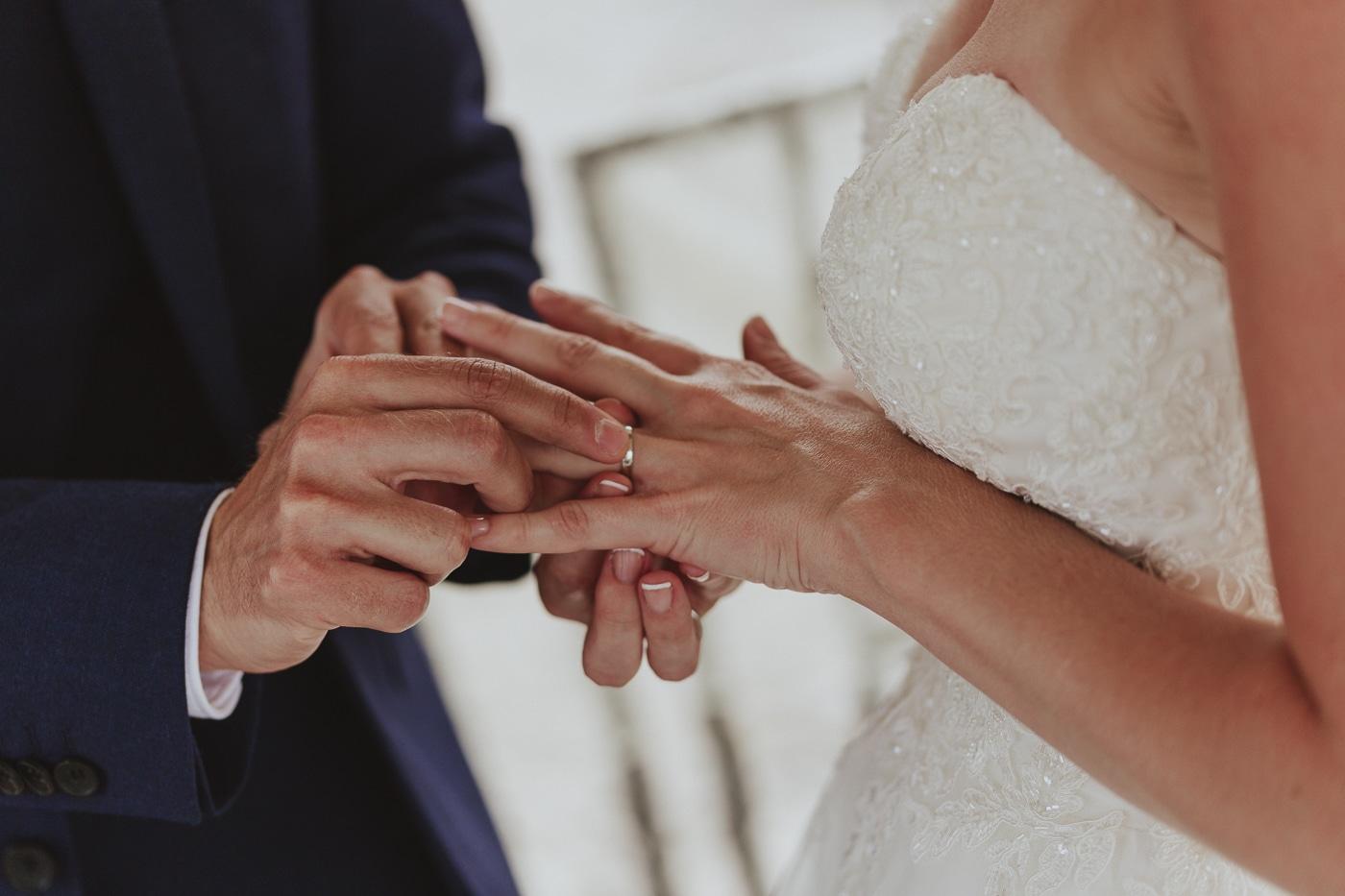 Groom putting white gold wedding ring on brides left ring finger