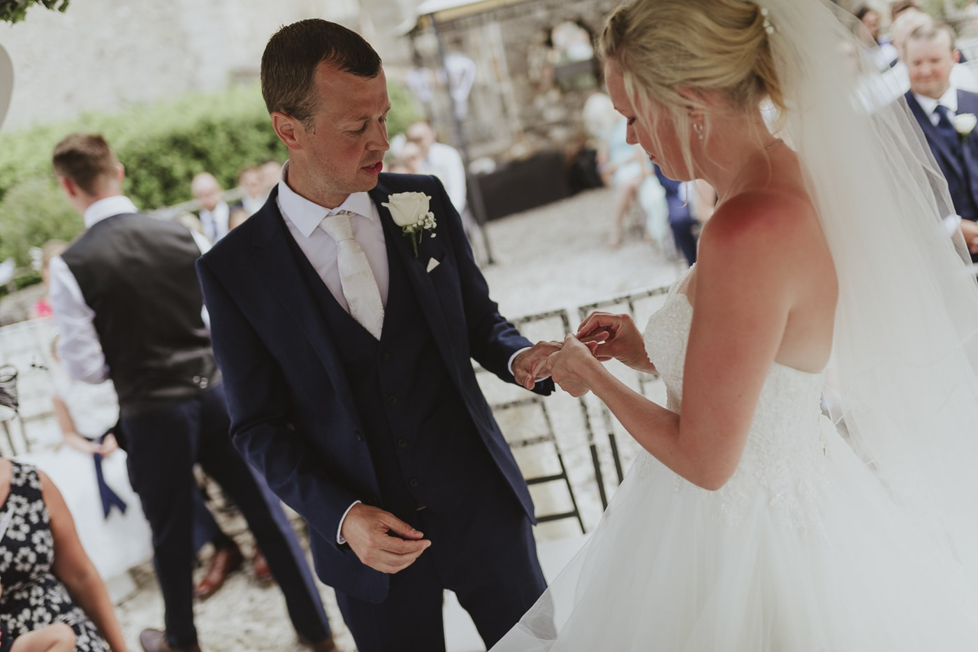 Bride in white dress putting ring on grooms finger during wedding vows