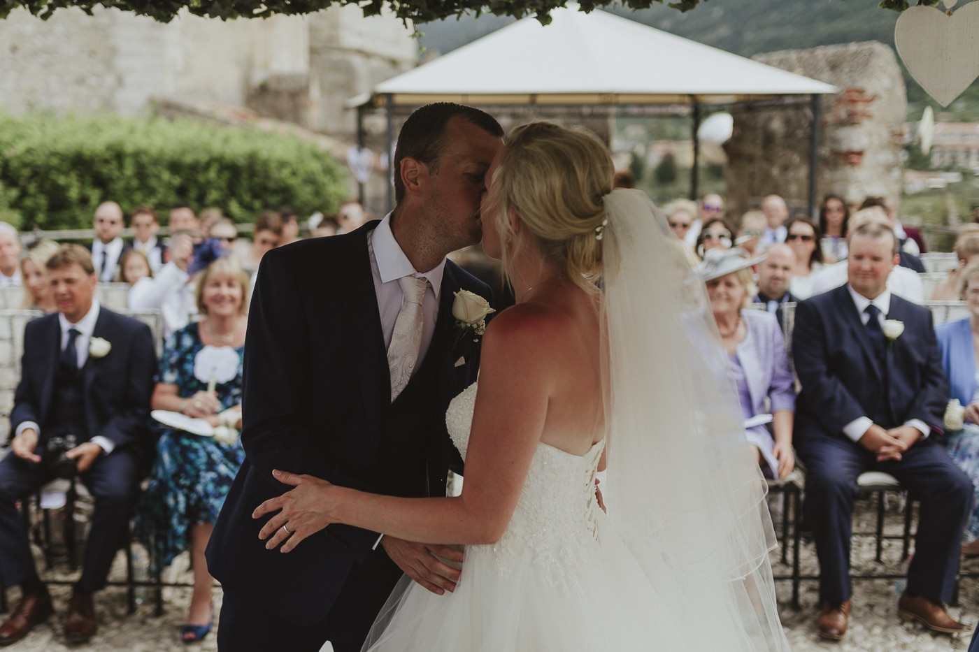Bride with veil in her hair kisses husband in suit and white tie with flower in front of happy wedding guests