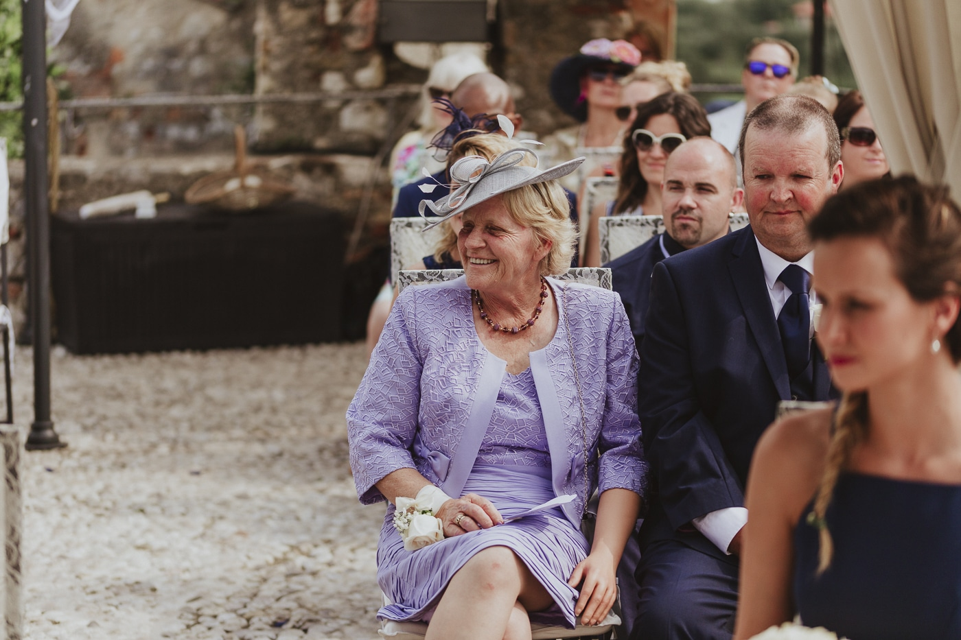 Blonde woman in purple dress and jacket with hat sitting at the front of the wedding guests