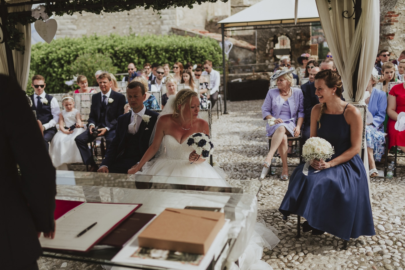 Bride sitting with flowers in her hand smiling at a bridesmaid in a blue dress and white flowers in her hands with wedding guests in the background