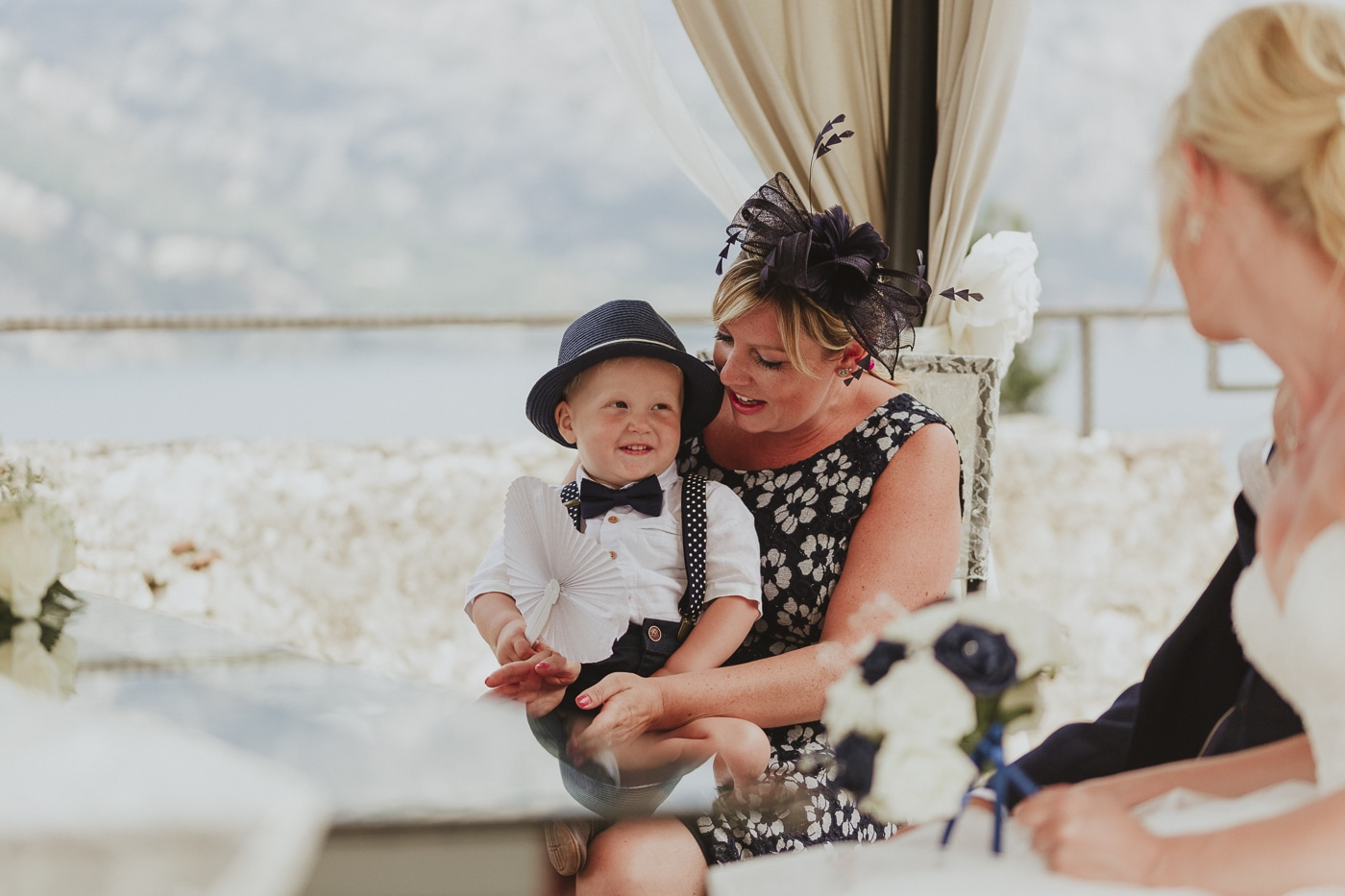 Small child with hat on sitting on lap of a lady in a flowery dress with a fascinator in hair