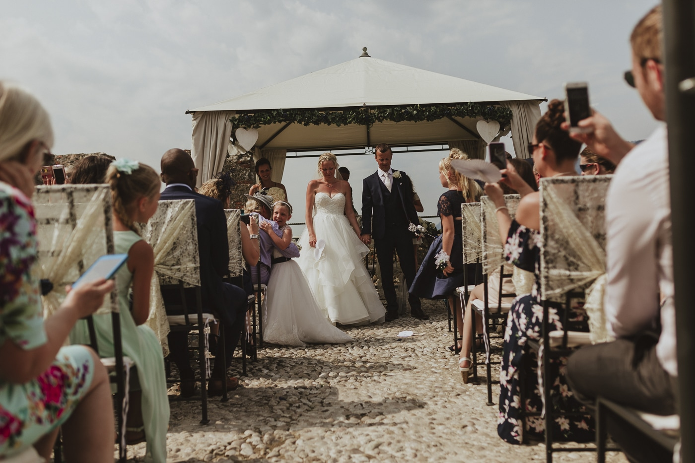 Bride and groom standing at the front of the aisle under a canopy with wedding guests looking on