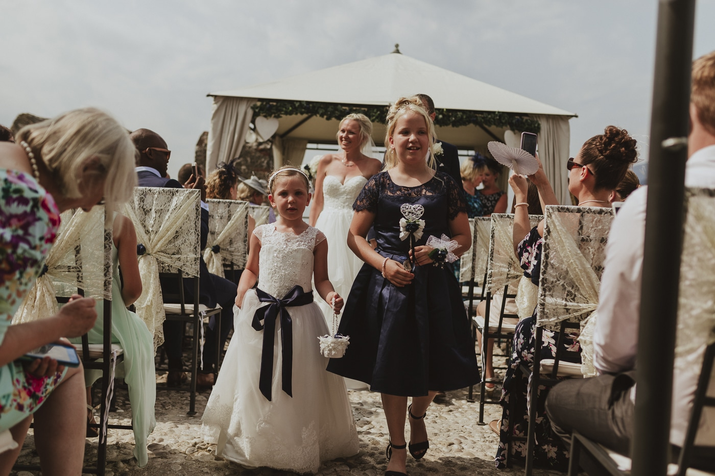 Bridesmaid and flower girl walking up the wedding aisle with lace on chairs and bride in the background