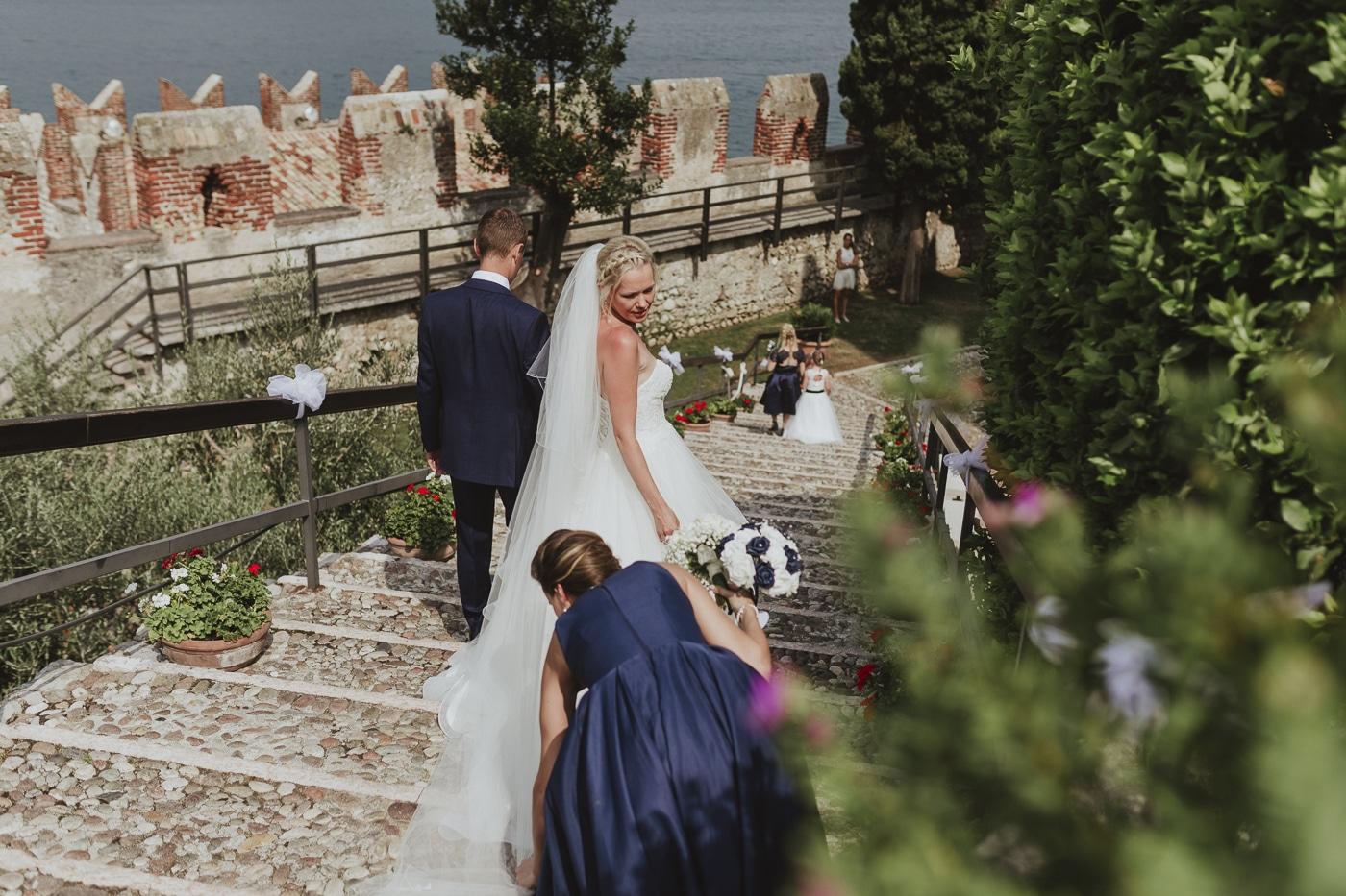 Bridesmaid adjusting brides dress as she and a man walk down stone steps