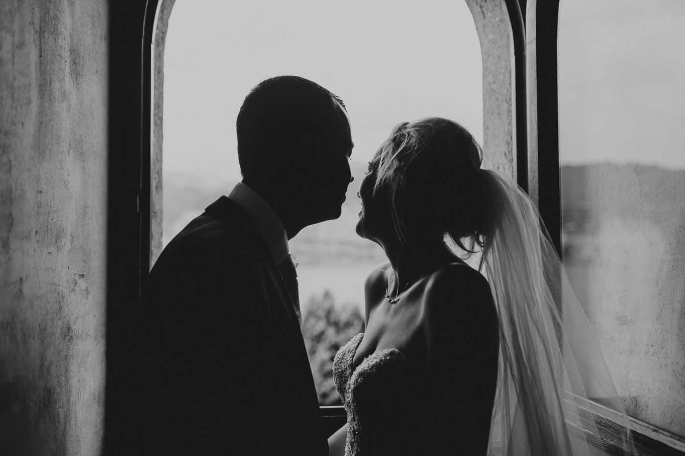 Black and white image of bride and groom standing in window laughing and overlooking lake garda