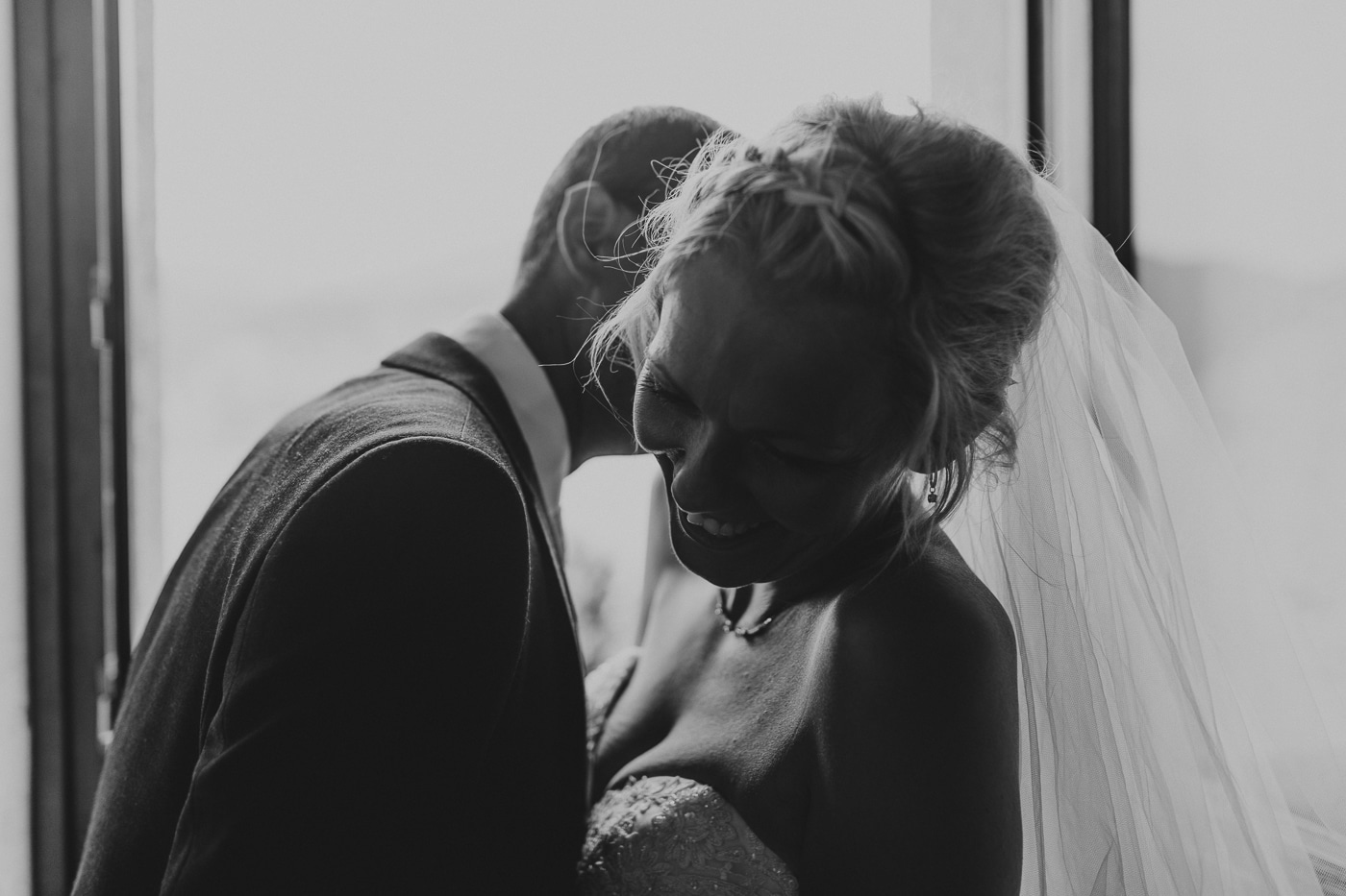 Bride with braid and veil in hair laughing as husband whispers in her ear