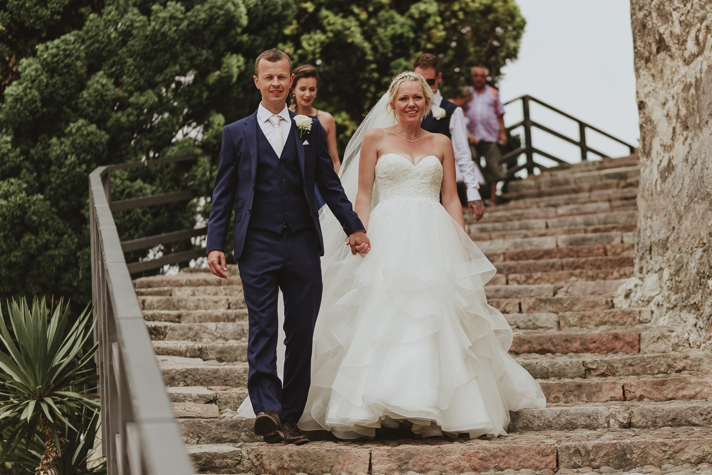 Bride and groom walking down the stone stairs with other wedding guests behind them and metal railings and trees in the background