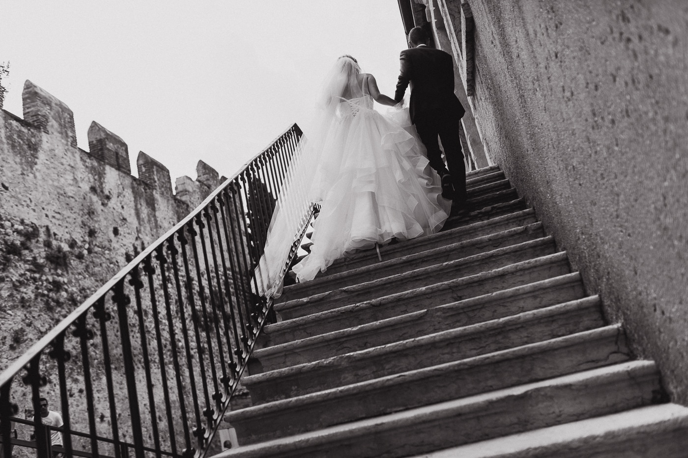 Man and woman climbing old stone steps with bridal dress swaying in the breeze