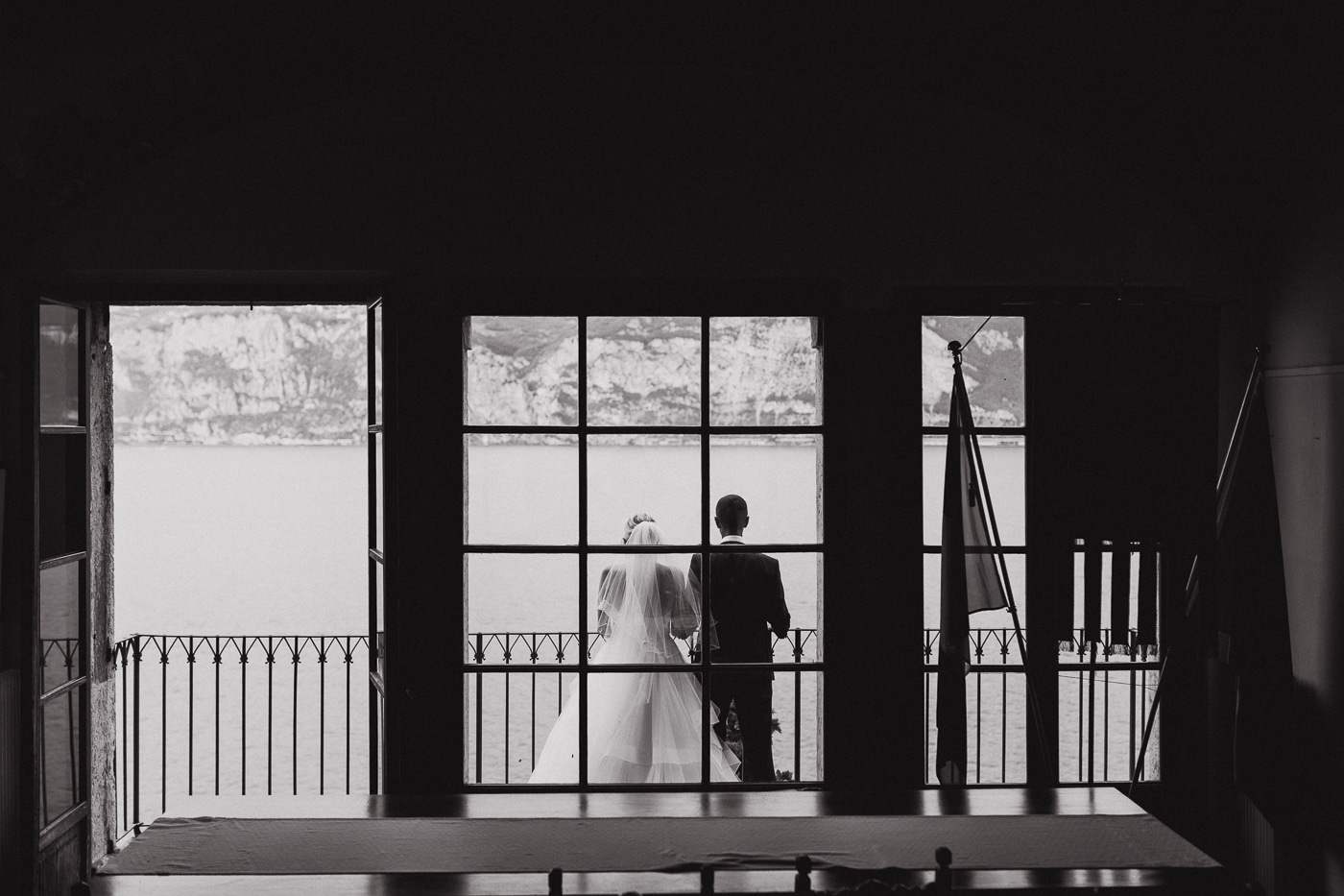 Bride in veil and groom standing on balcony overlooking lake garda and mountains with windows in the foreground