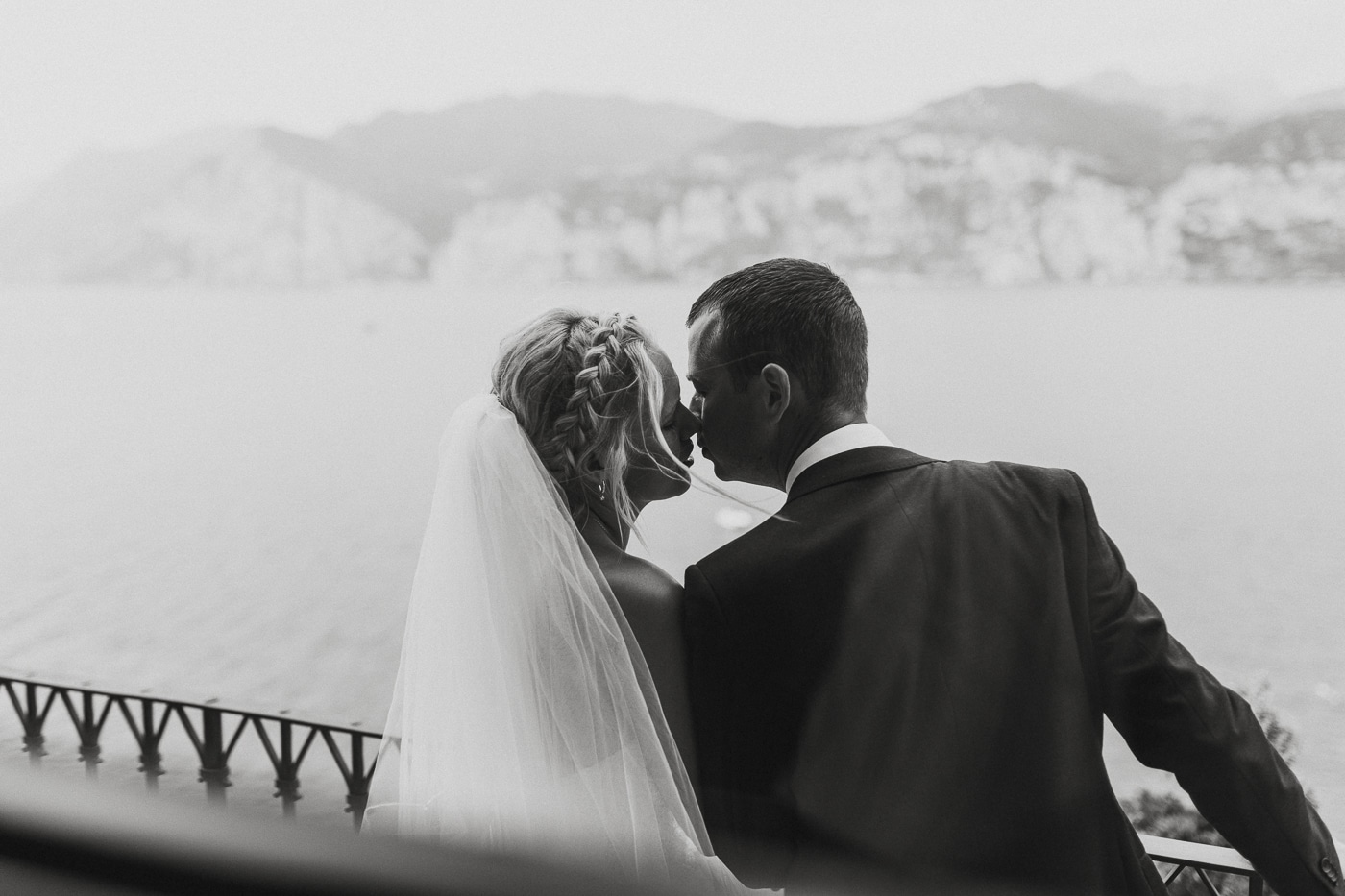 Bride with braided hair and veil kissing suited groom overlooking lake garda in italy