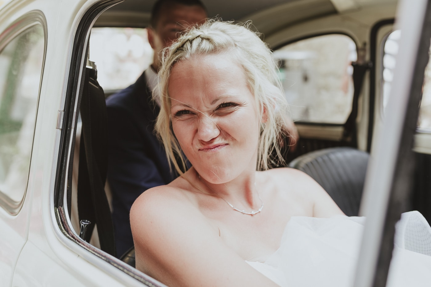 Bride with braided hair screwing up face as she attempts to park vintage car with new husband in the back seat