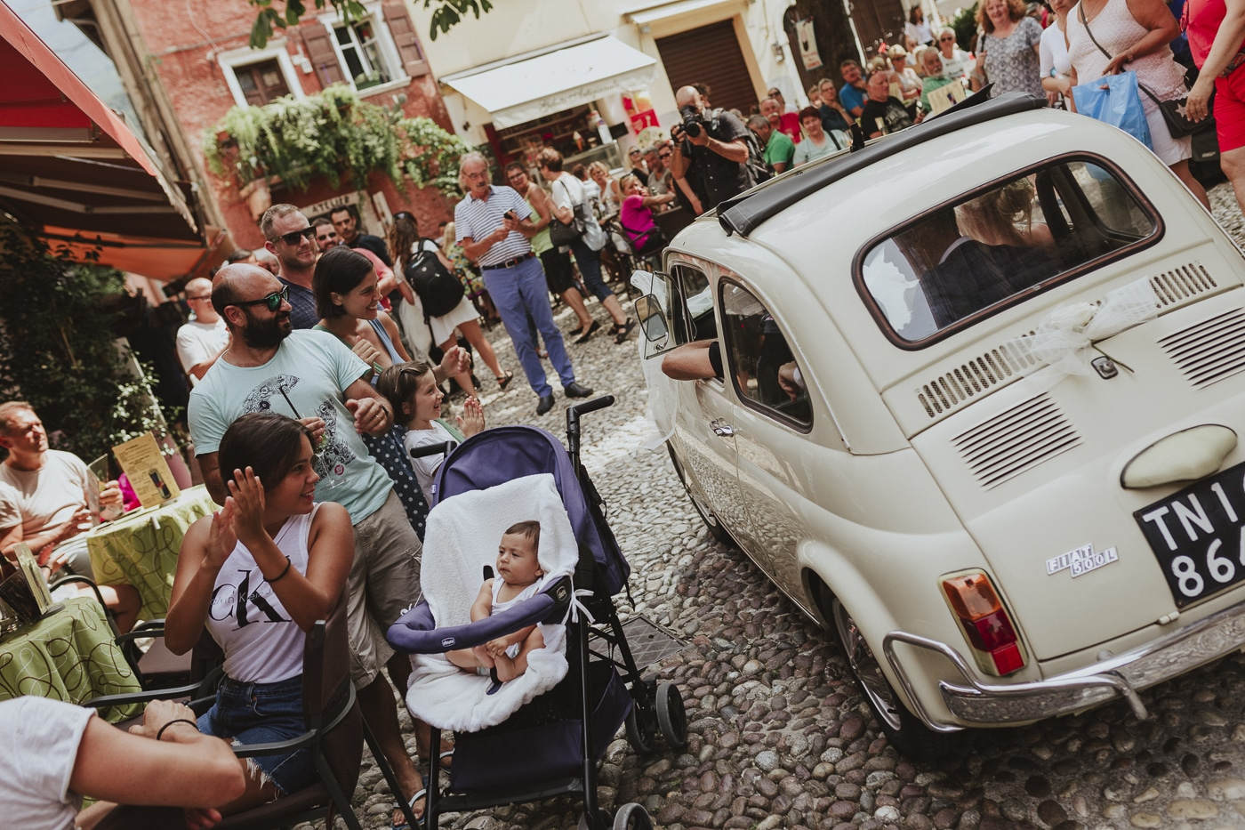 Vintage cream car driving along cobbled streets around local people and tourists