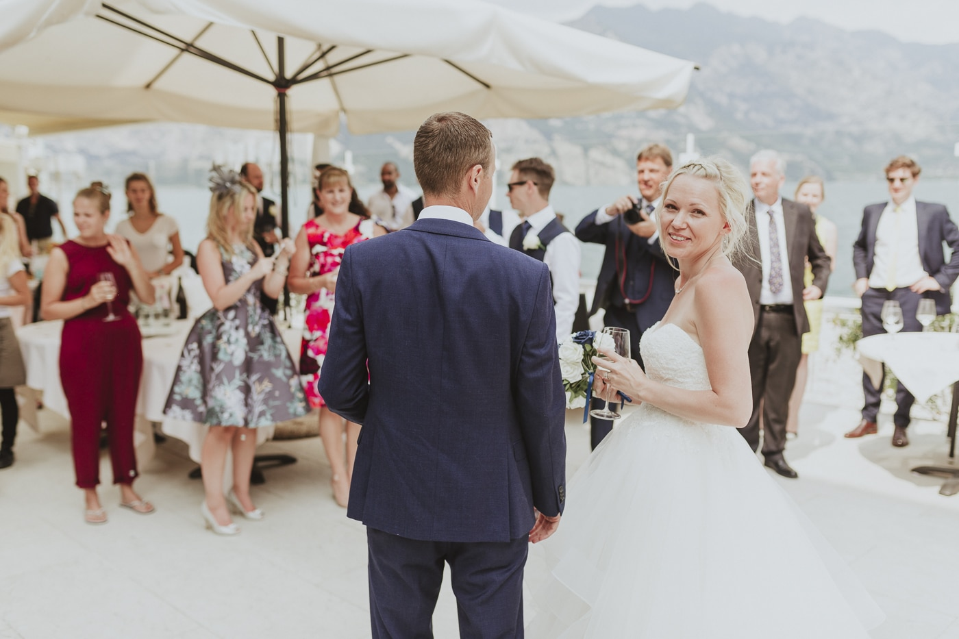 Bride and groom looking back as they walk into their wedding reception with all their guests and mountains in the background by Joshua Wyborn
