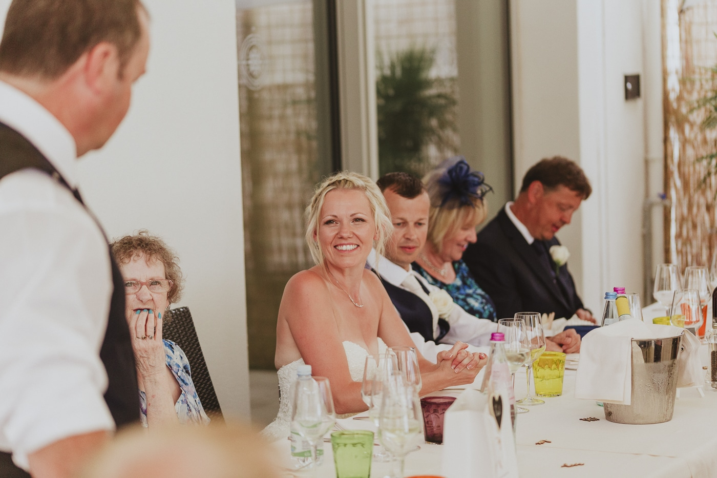 Bride and guests smiling with champagne bucket on table and speeches happening by Joshua Wyborn
