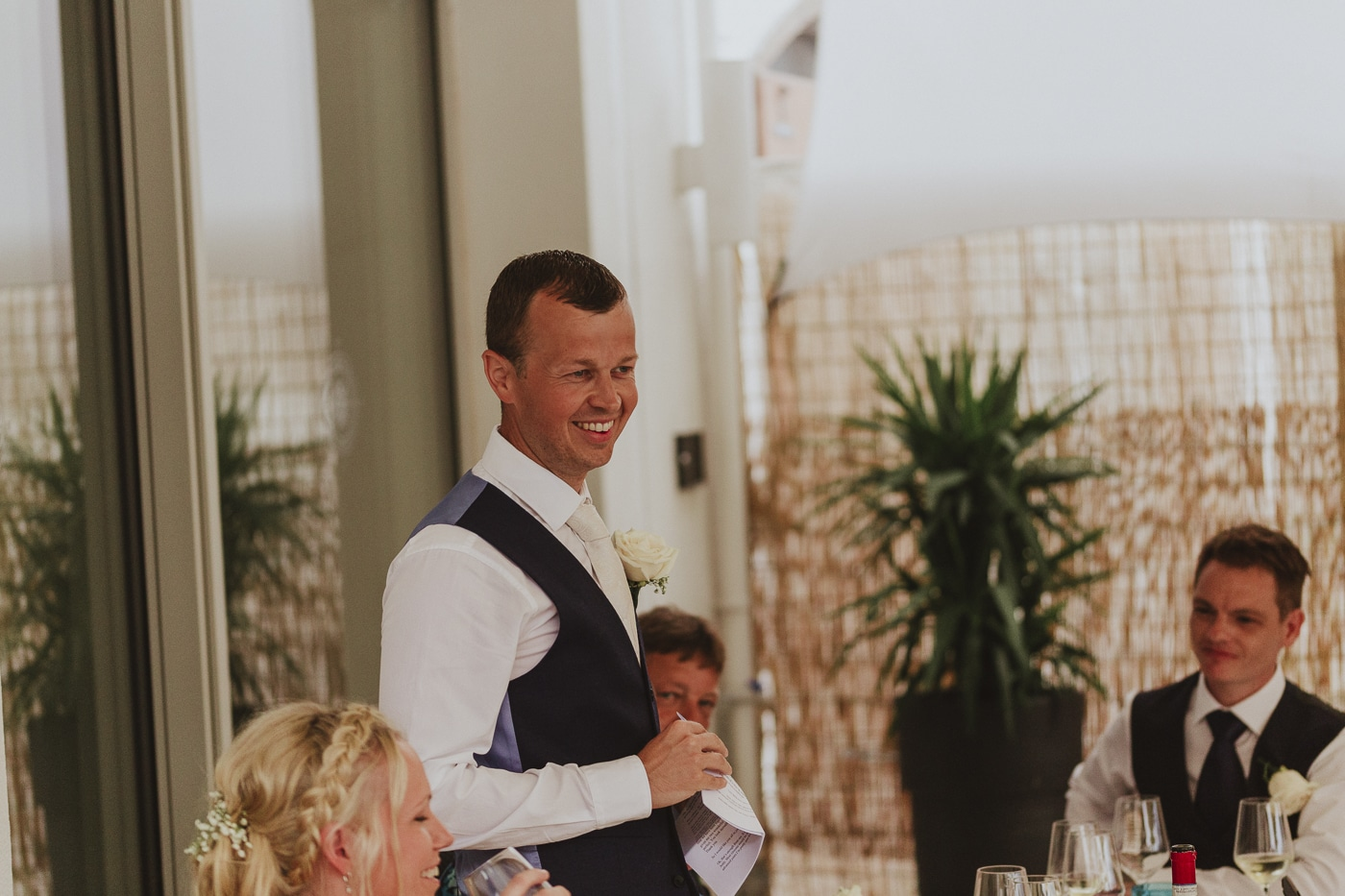 Groom in waistcoat standing up during dinner and drinks doing speech by Joshua Wyborn