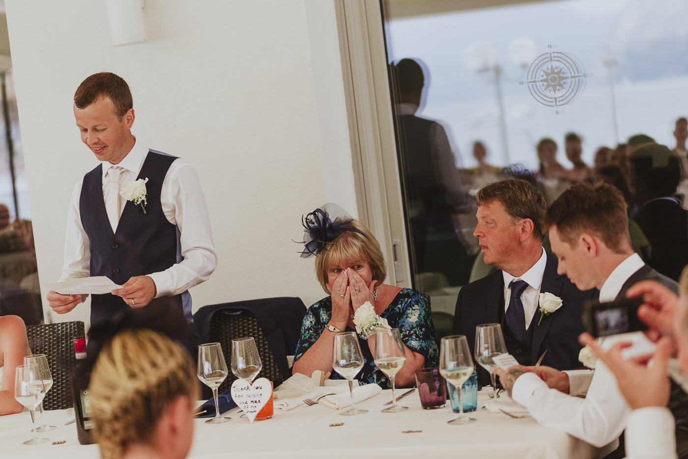 Man in waistcoat standing up during wedding speech while guests look on by Joshua Wyborn