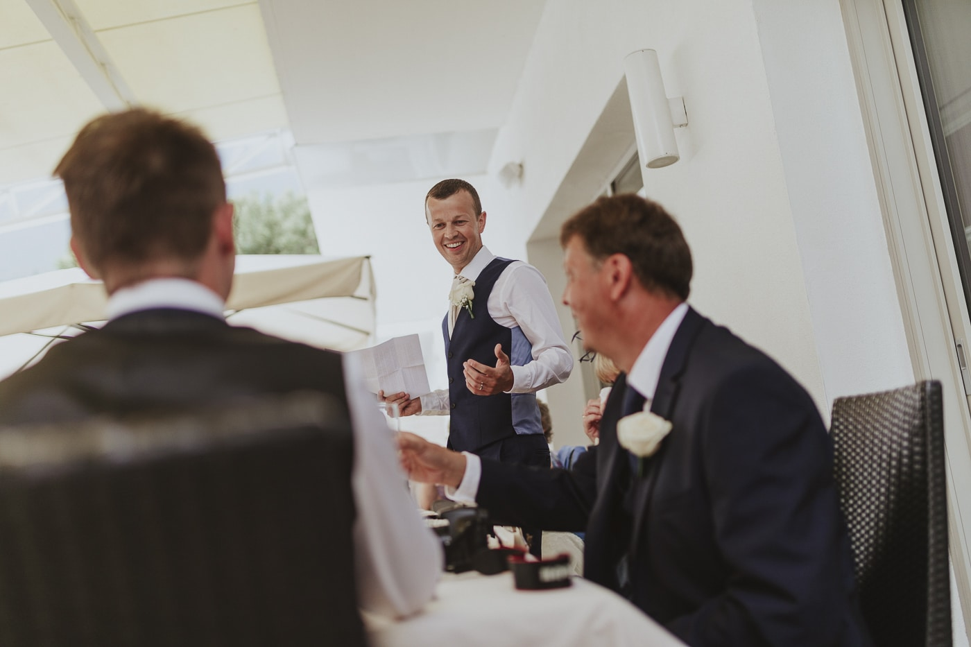 Three suited men during speeches smiling and gesturing by Joshua Wyborn