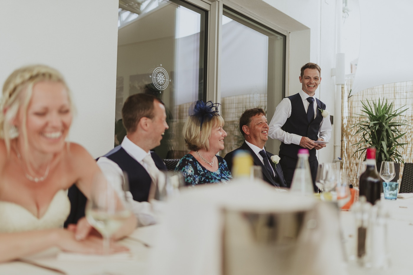 Wedding guests at table during reception speeches with bottles of drink in the foreground by Joshua Wyborn