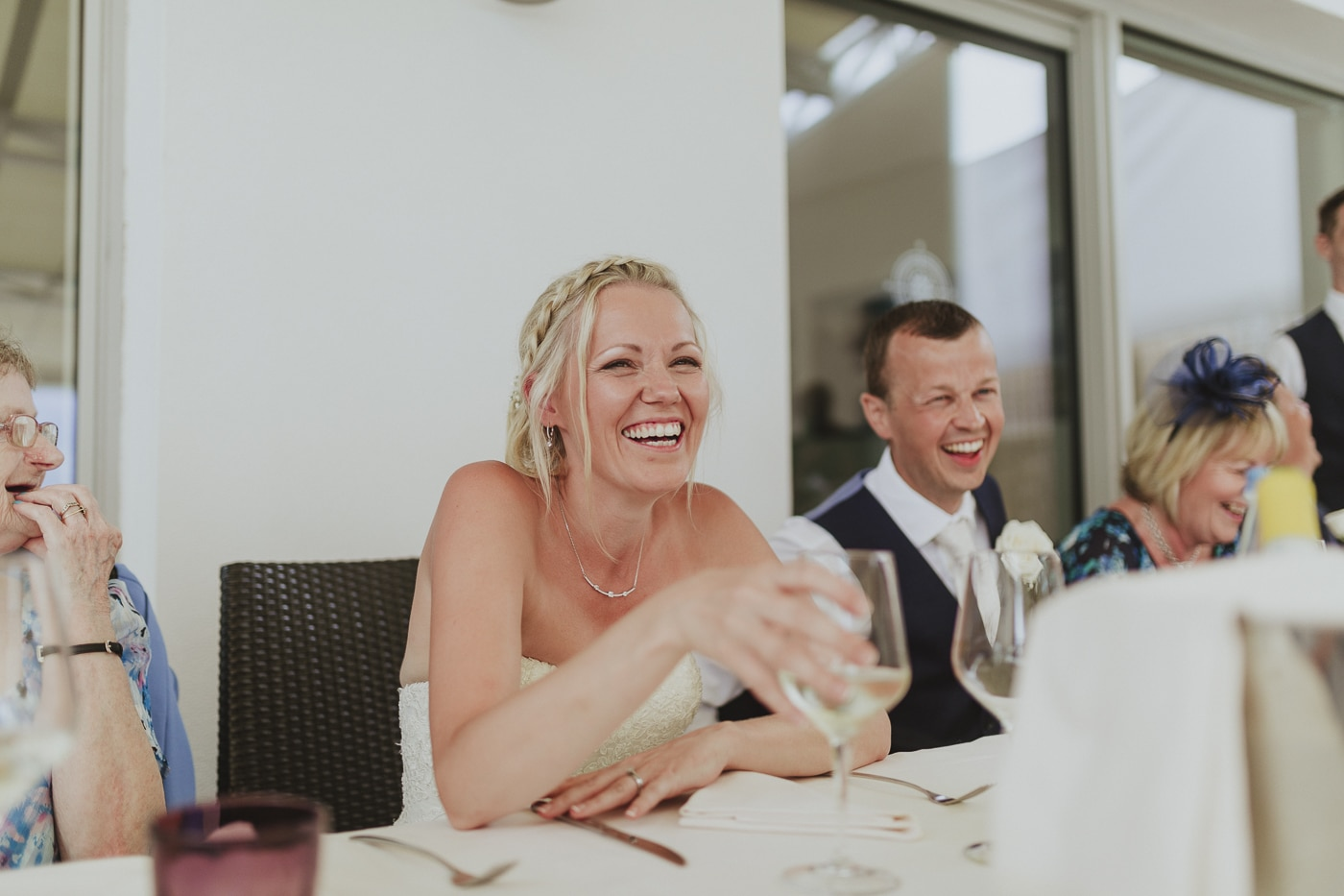 Bride with braids in her hair and a glass of wine in her hand laughs along with husband and guests by Joshua Wyborn