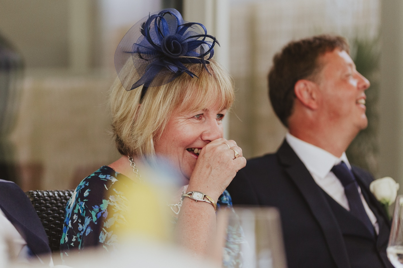 woman in blue fascinator and gold jewellery laughs along with man by Joshua Wyborn