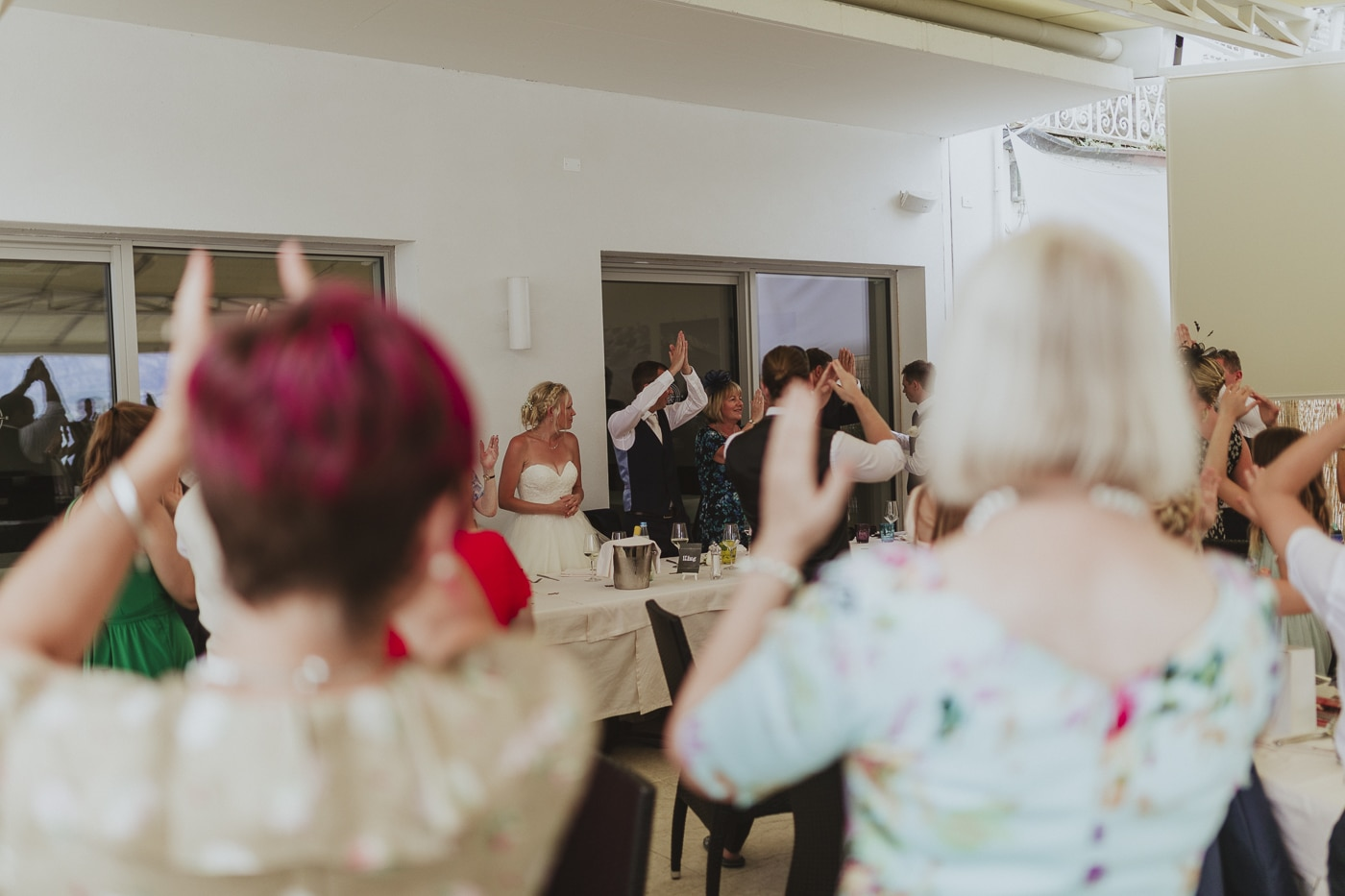 Guests and groom clapping whilst bride stands watching during wedding reception by Joshua Wyborn