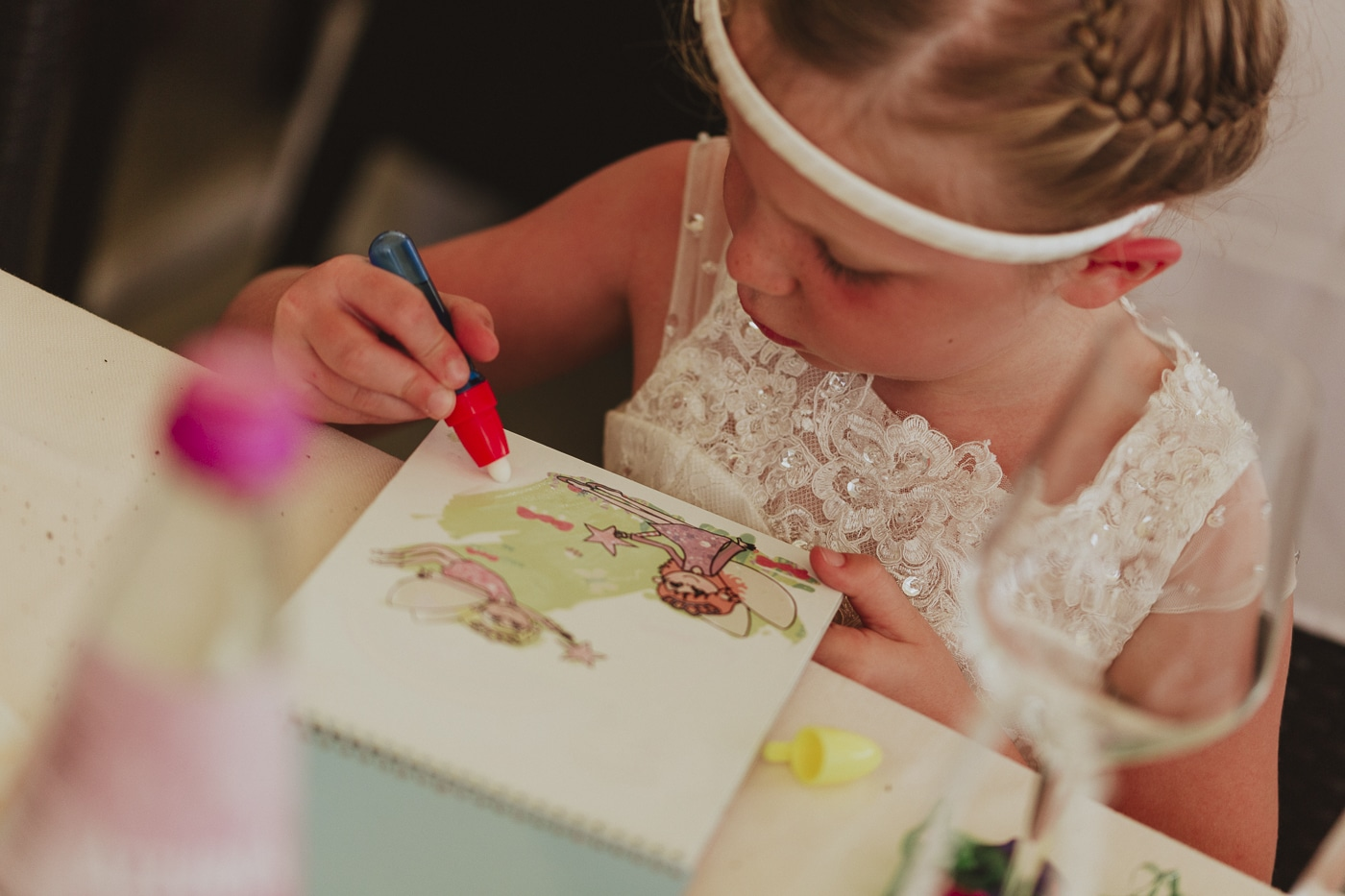 Young child colouring dressed in white bridesmaid dress and white headband by Joshua Wyborn