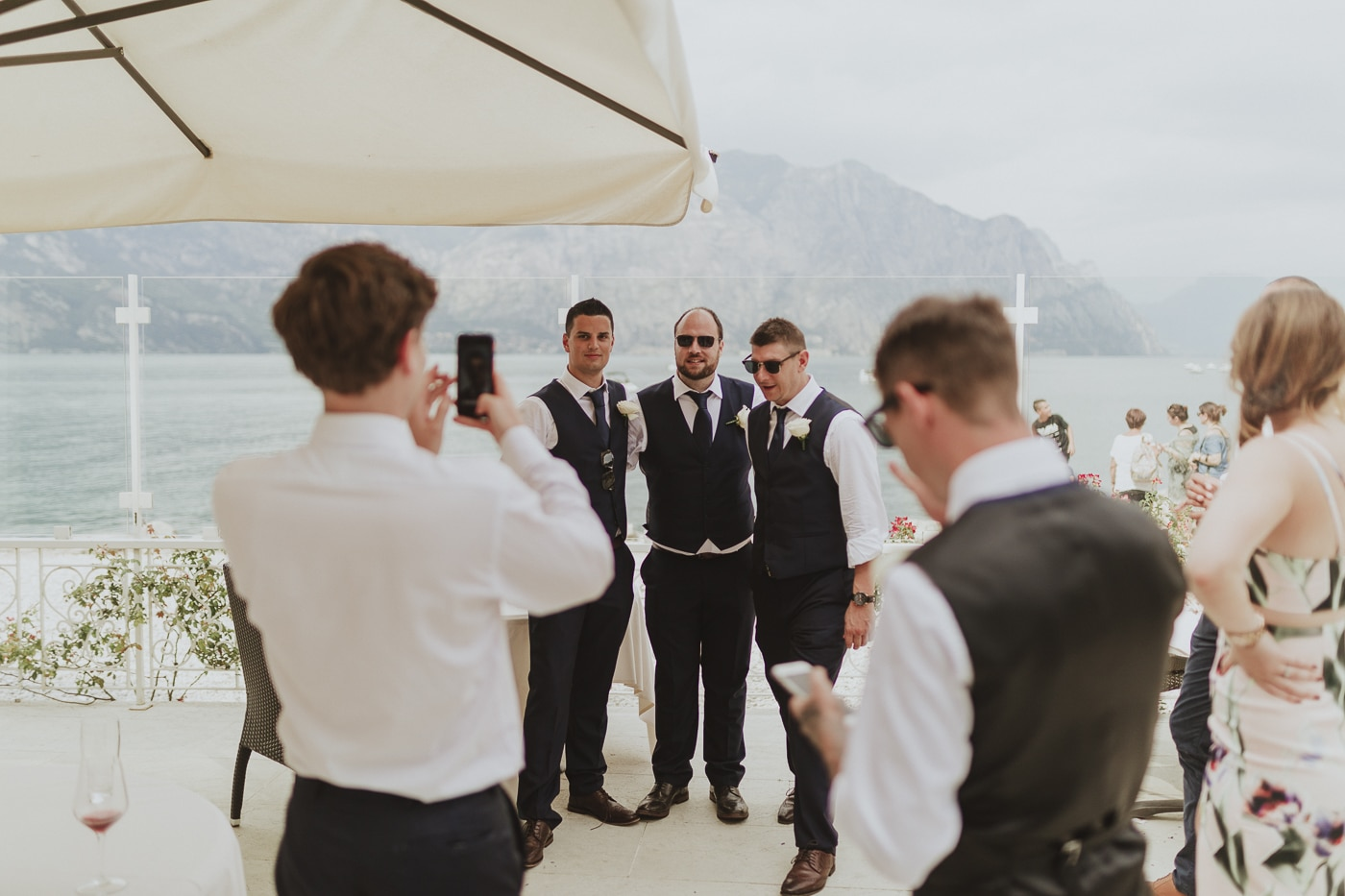 Three men in suits and waistcoats having a photo infront of the mountain and lake scenery by Joshua Wyborn