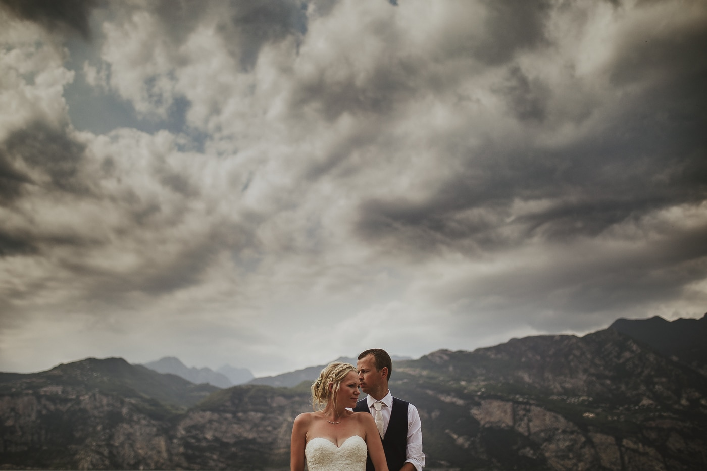 Bride with braided hair and groom in waistcoat standing amid mountains and grey cloudy skies by Joshua Wyborn