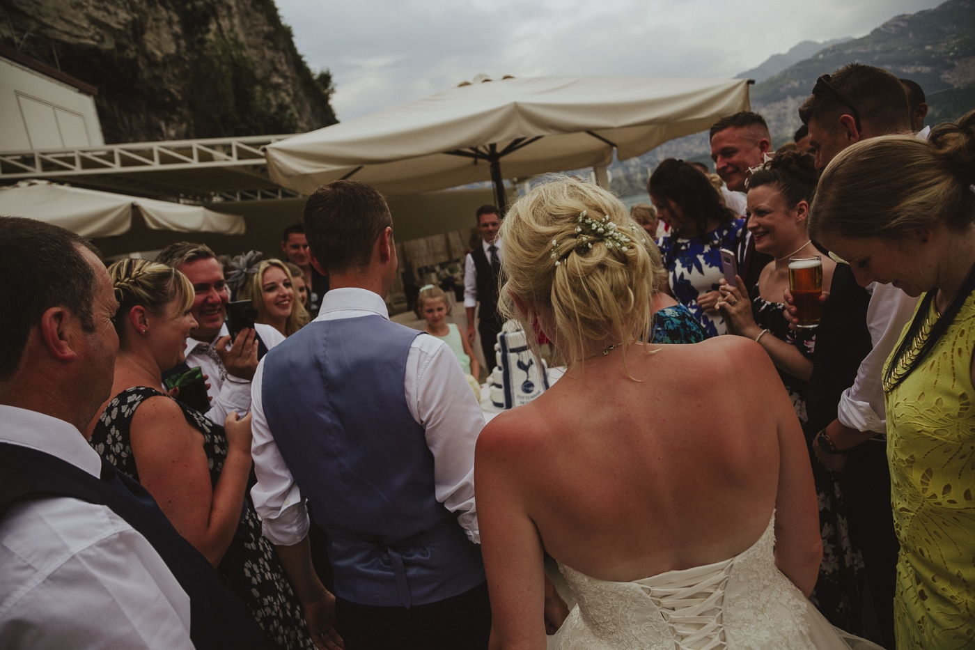 Bride with flowers in hair and corset back dress with groom in blue waistcoat walking away from the photographer to the umbrella and wedding cake surrounded by mountains by Joshua Wyborn
