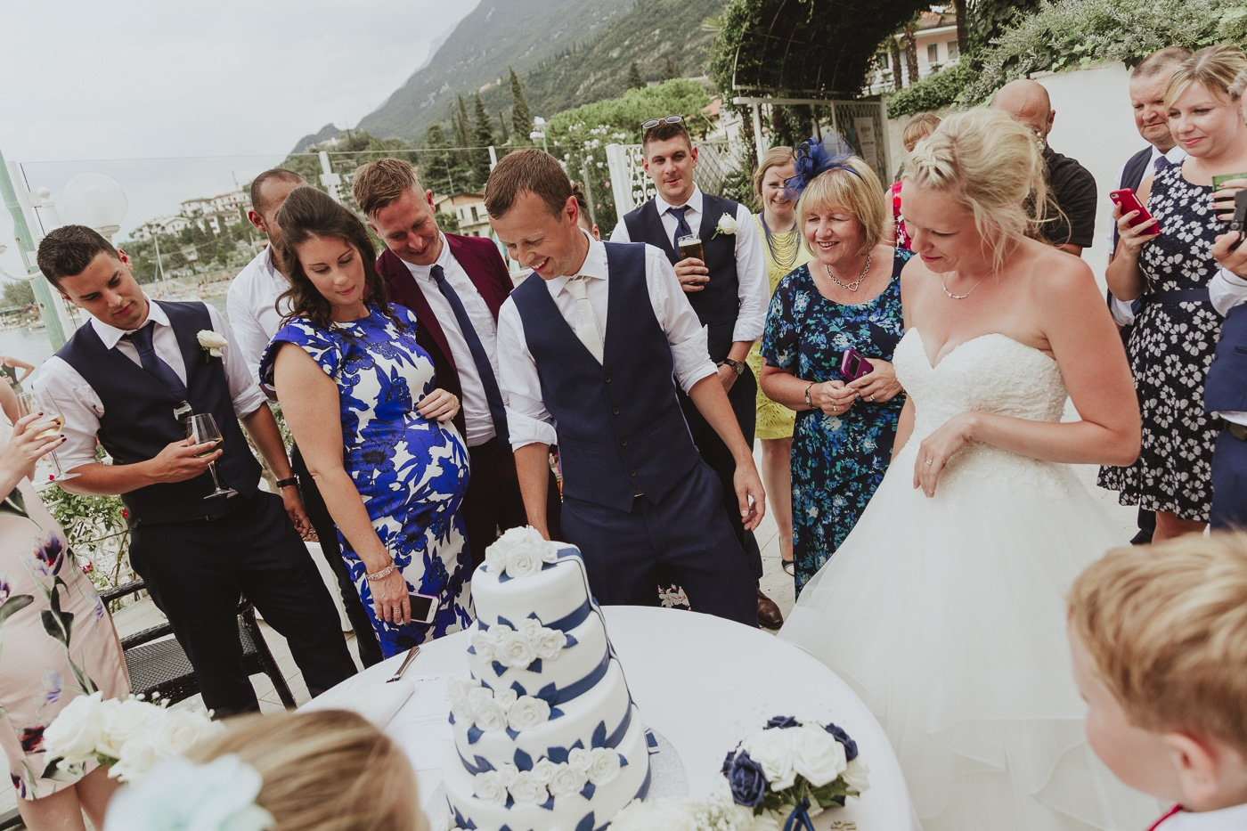 blue and white wedding cake with flowers cascading down it surrounded by bride, groom and guests in wedding attire by Joshua Wyborn