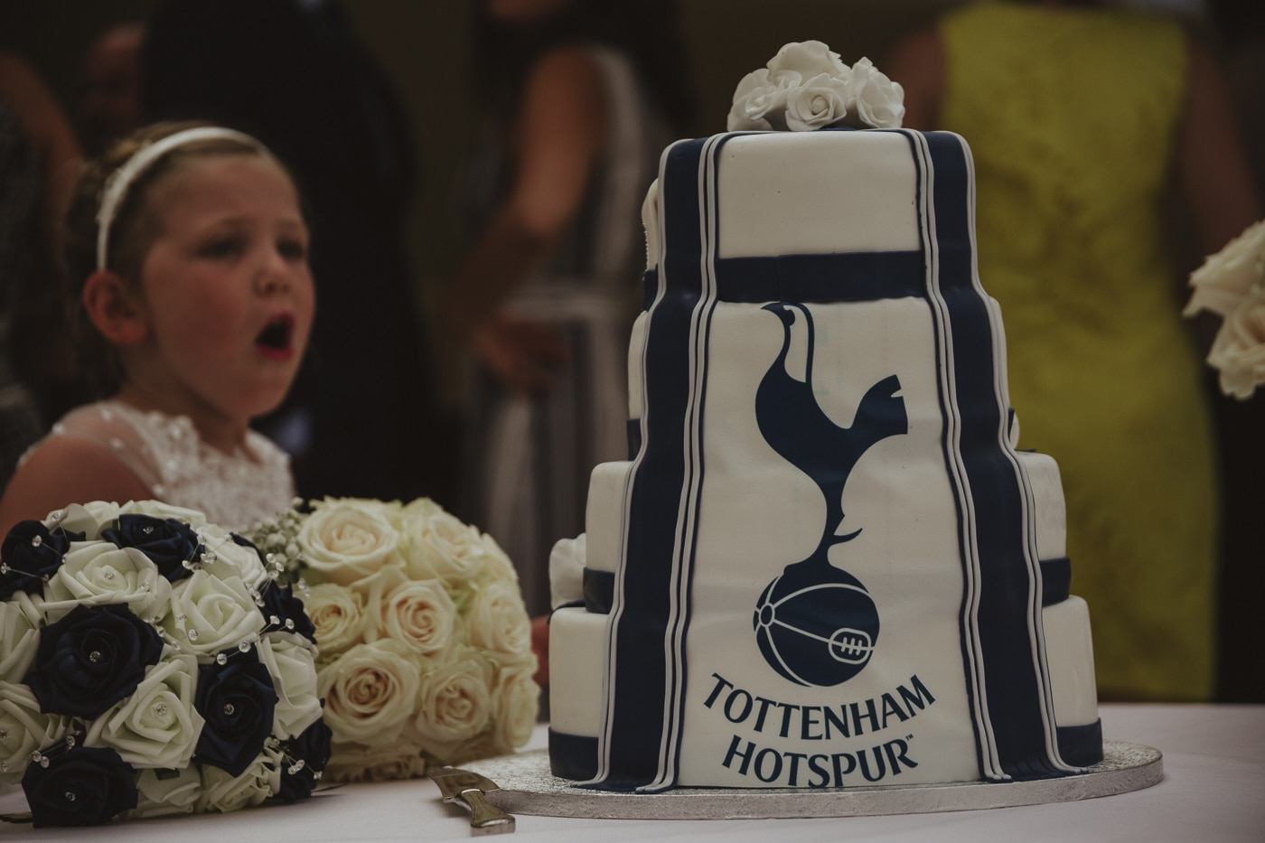 Tottenham hotspur wedding cake with flowers on the top and by the side and a surprised looking bridesmaid in the background by Joshua Wyborn