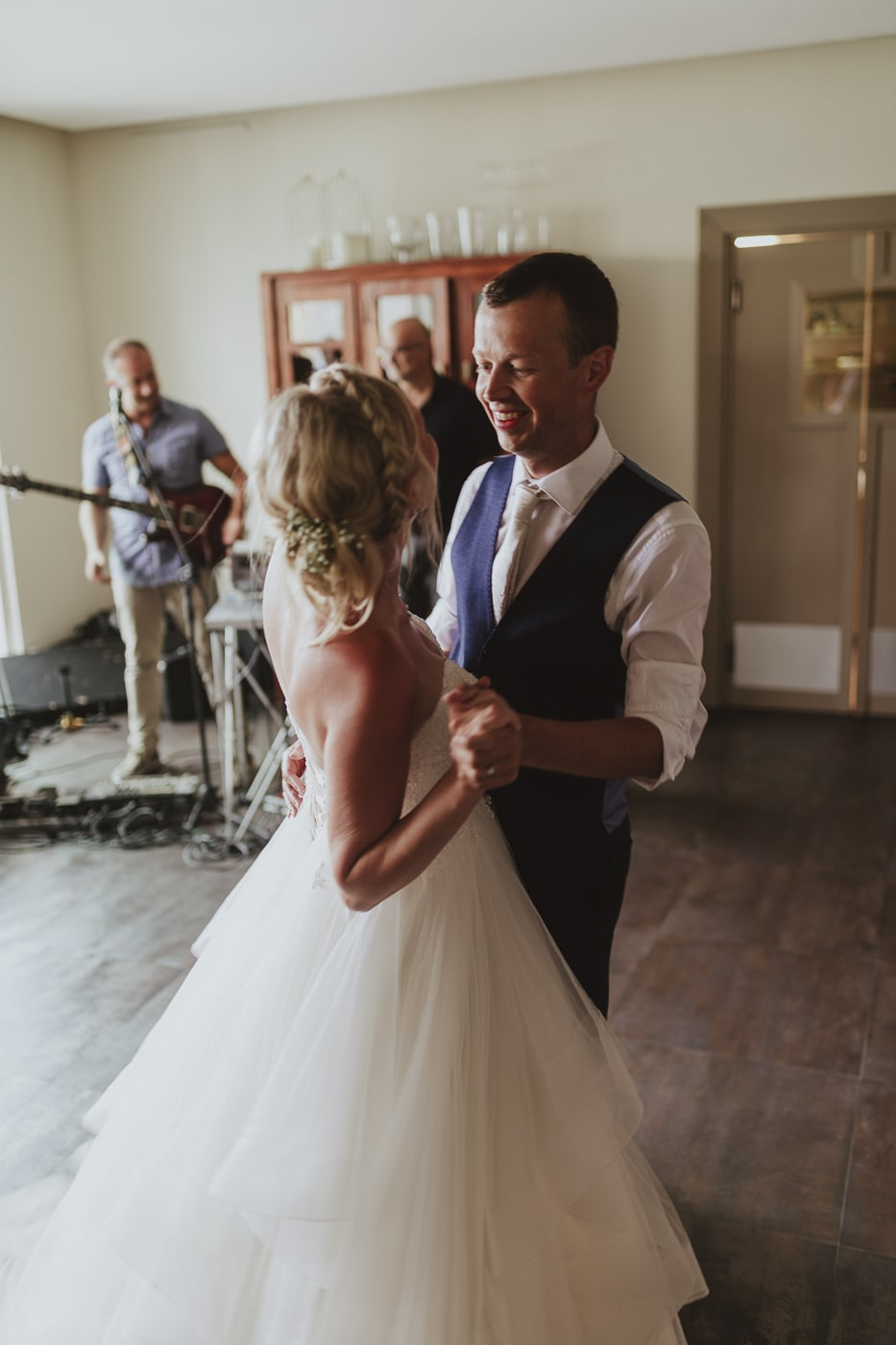 Bride with braided hair and white tulle dress dancing with man in white shirt and blue waistcoat with band playing in the background by Joshua Wyborn