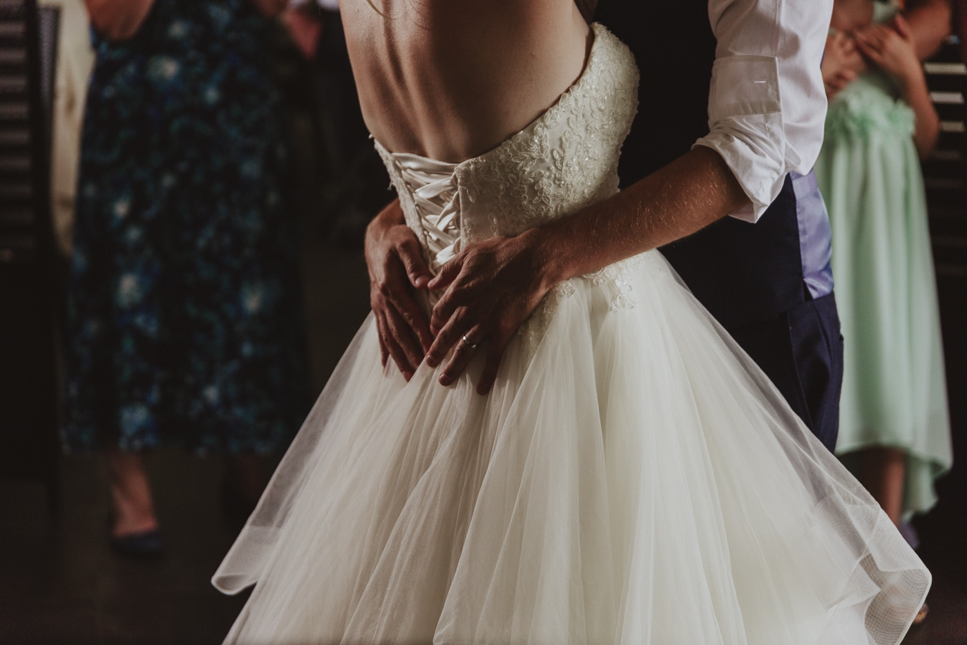 Grooms hands on brides white dress with corset back and tulle skirt by Joshua Wyborn