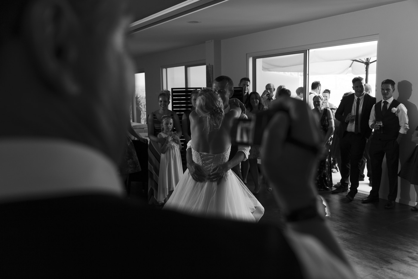 Dancing bride and groom while being videoed on the dancefloor with guests surrounding them by Joshua Wyborn